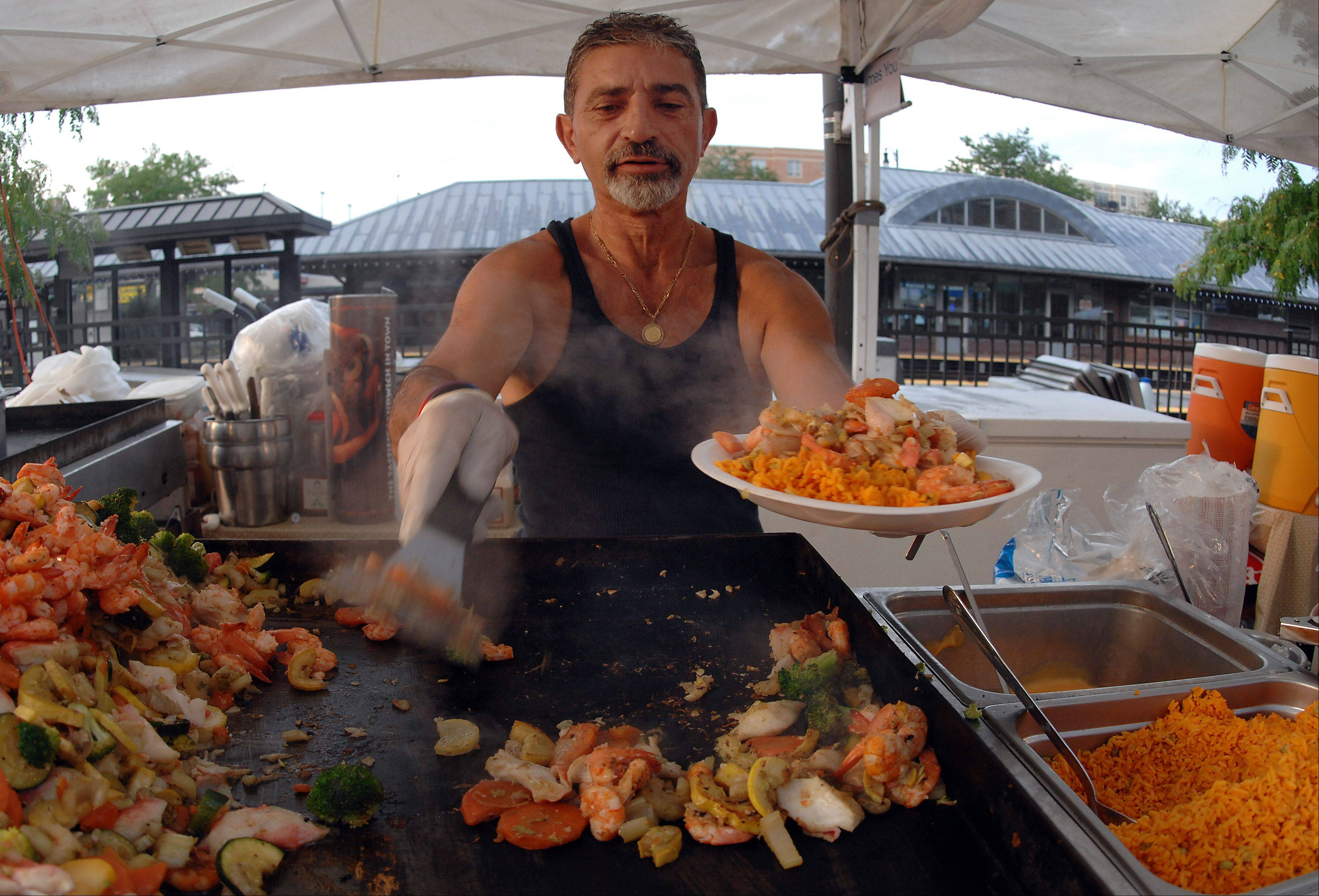 Telly Likoubis serves up his famous seafood combo platter to hungry patrons at last year's Des Plaines Summer Fling Festival. The festival will go on this year, though aldermen briefly discussed nixing it.