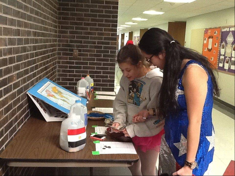 Maggie Sandner-Gialamas, left, of Lake Forest and Loren Ketelsen of Lincolnshire get their last-minute contributions into the world water day contest at Woodlands Academy of the Sacred Heart.