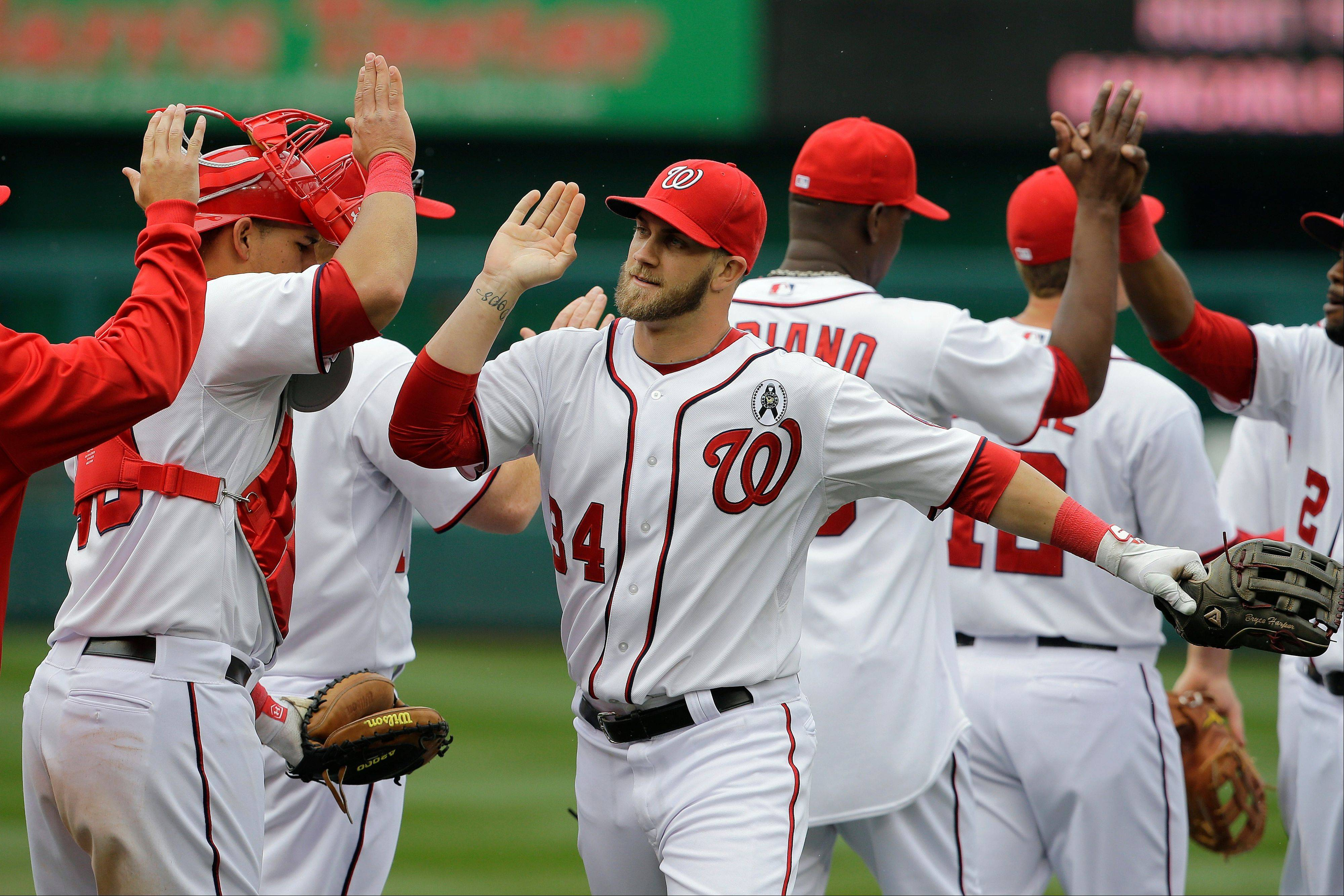 Nationals left fielder Bryce Harper (34) congratulates his teammates after a 2-0 victory over the Miami Marlins in the Opening Day game Monday in Washington.