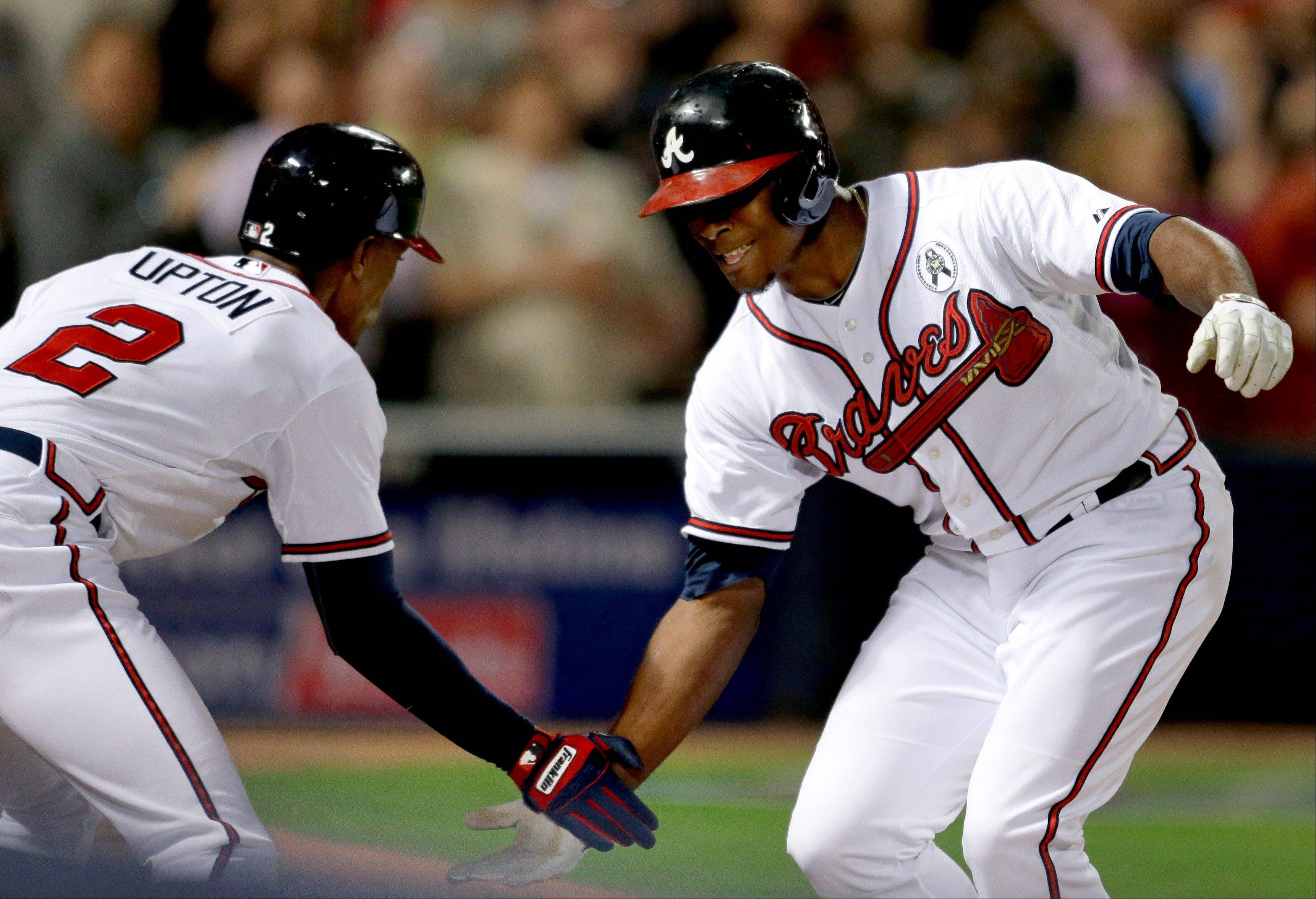 The Braves� Justin Upton, right, high-fives his brother and teammate B.J. Upton after hitting a home run in the fifth inning Monday against the Phillies.