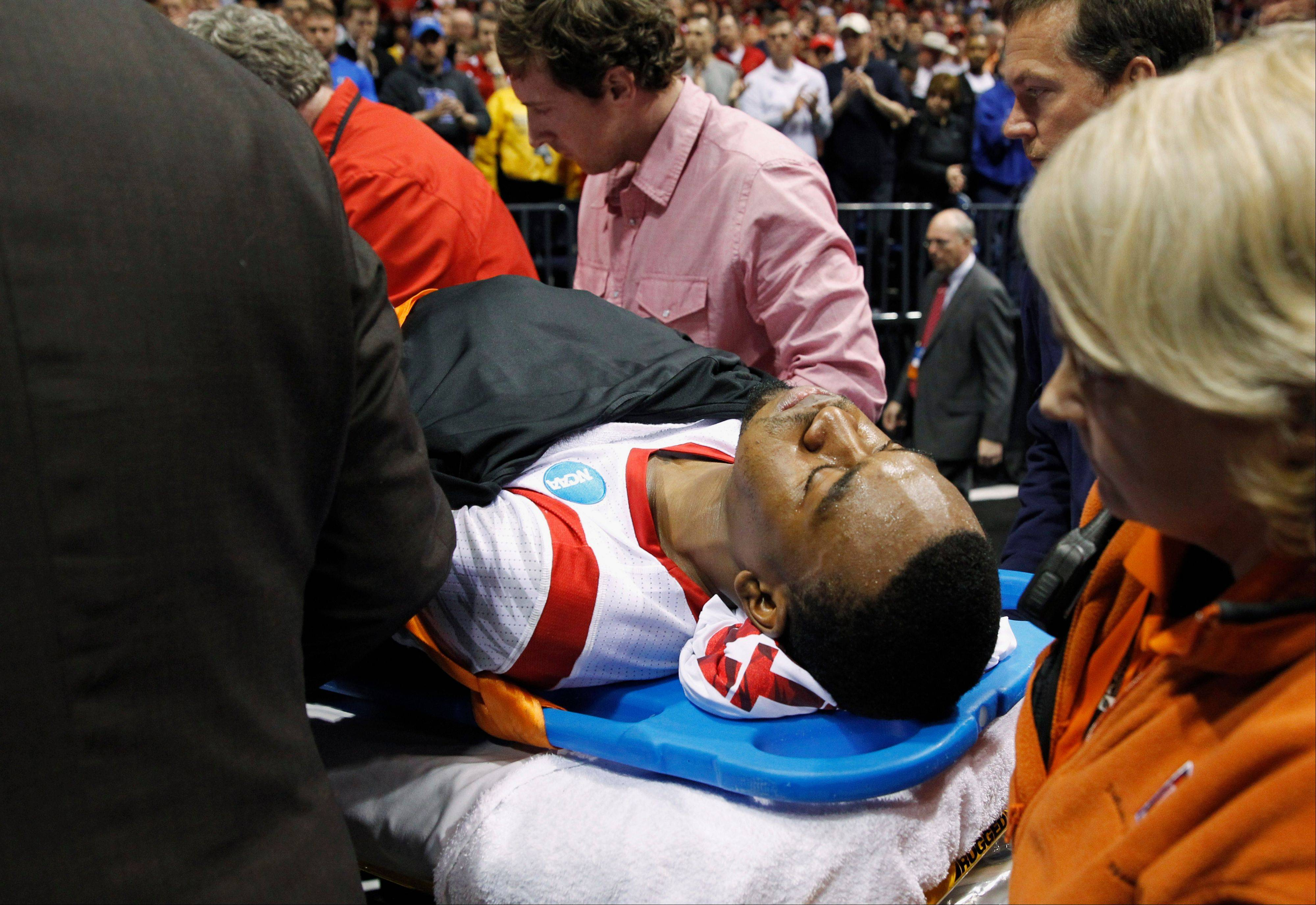 Louisville guard Kevin Ware is taken off of the court on a stretcher after his injury during the first half of the Midwest Regional final against Duke in the NCAA college basketball tournament Sunday.