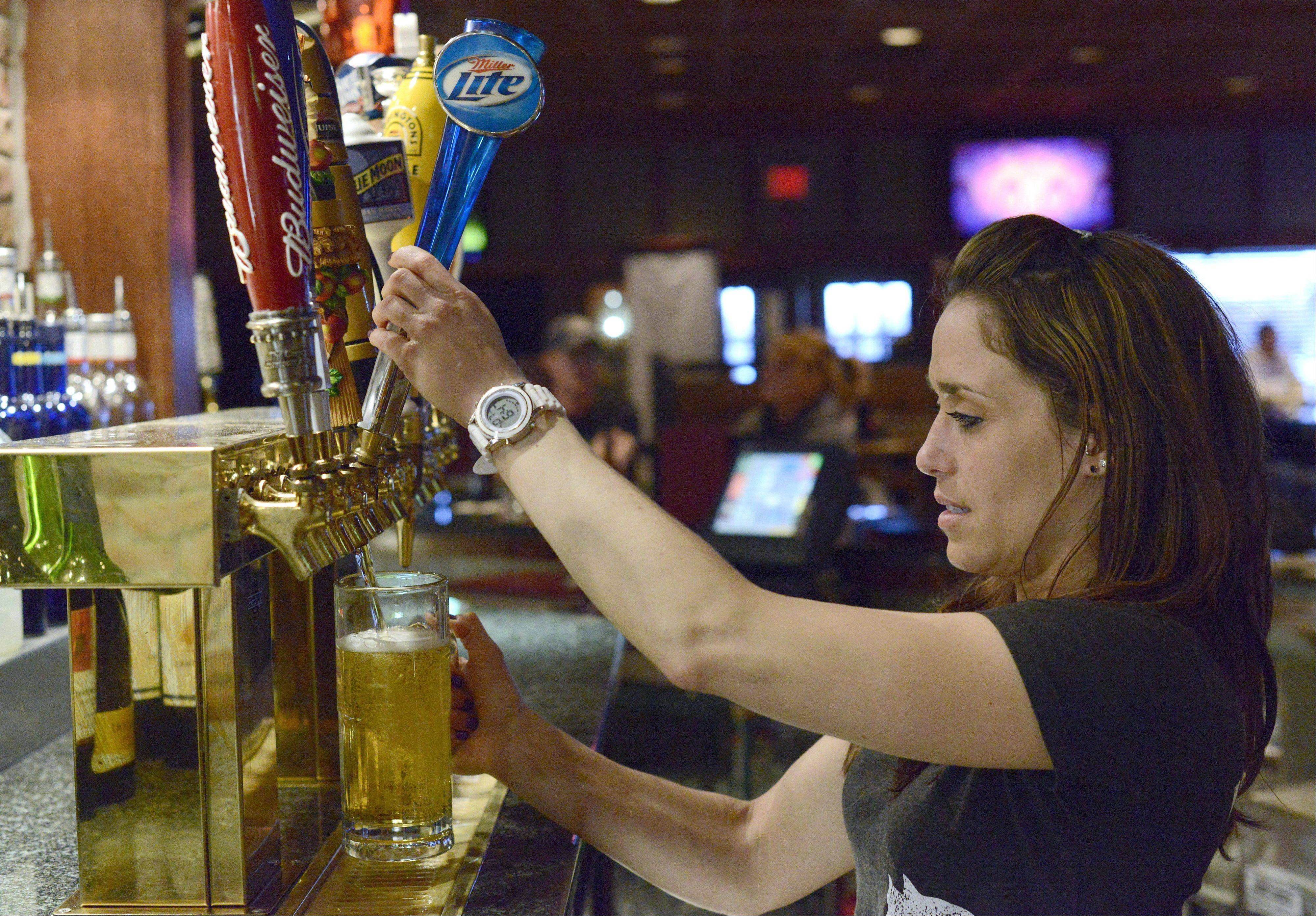 Bartender Sarah McCabe pours a beer at the Fox & Hound Sports Tavern in Arlington Heights.