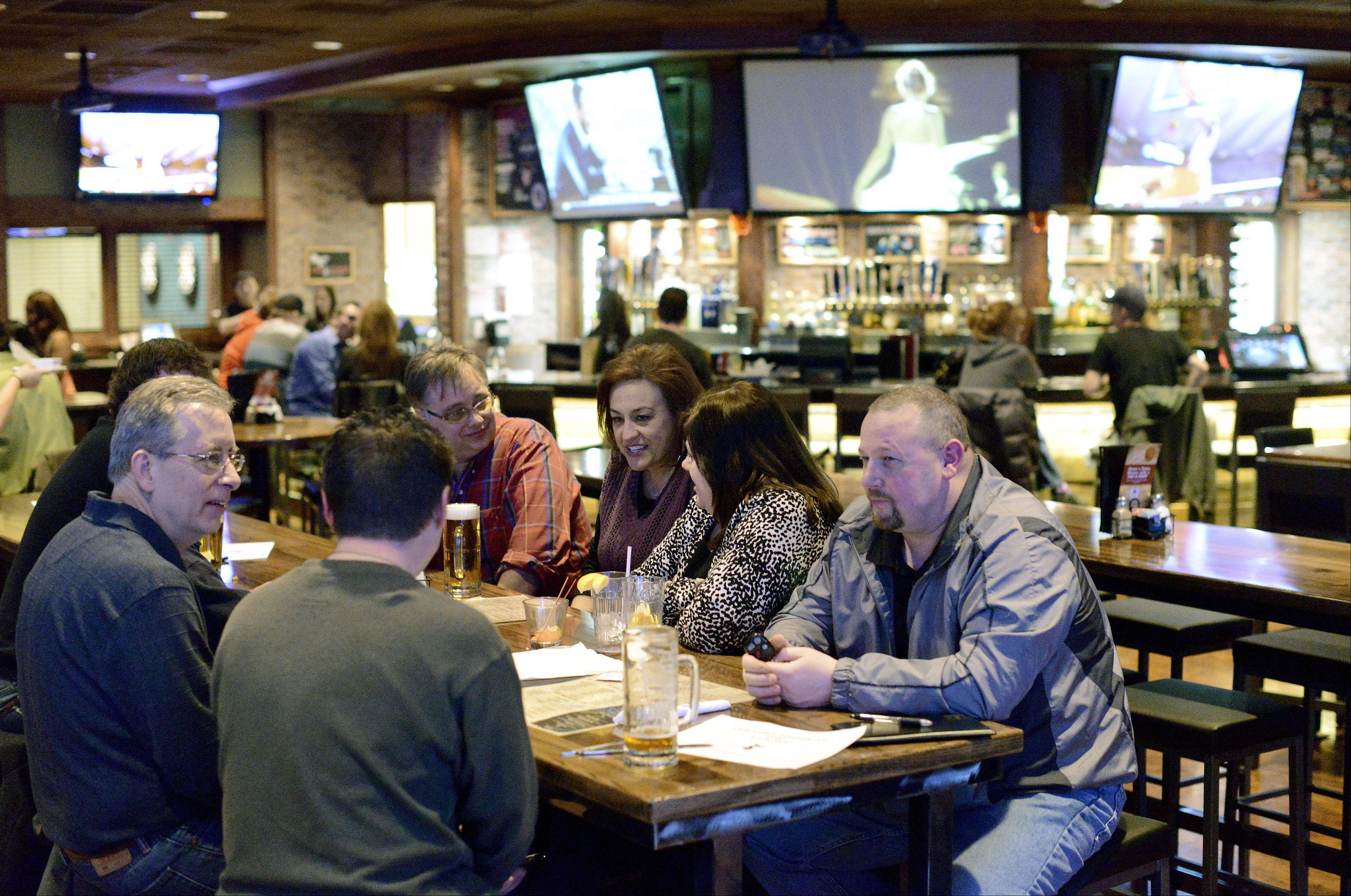 Patrons enjoy drinks at long tables at the Fox & Hound Sports Tavern in Arlington Heights.