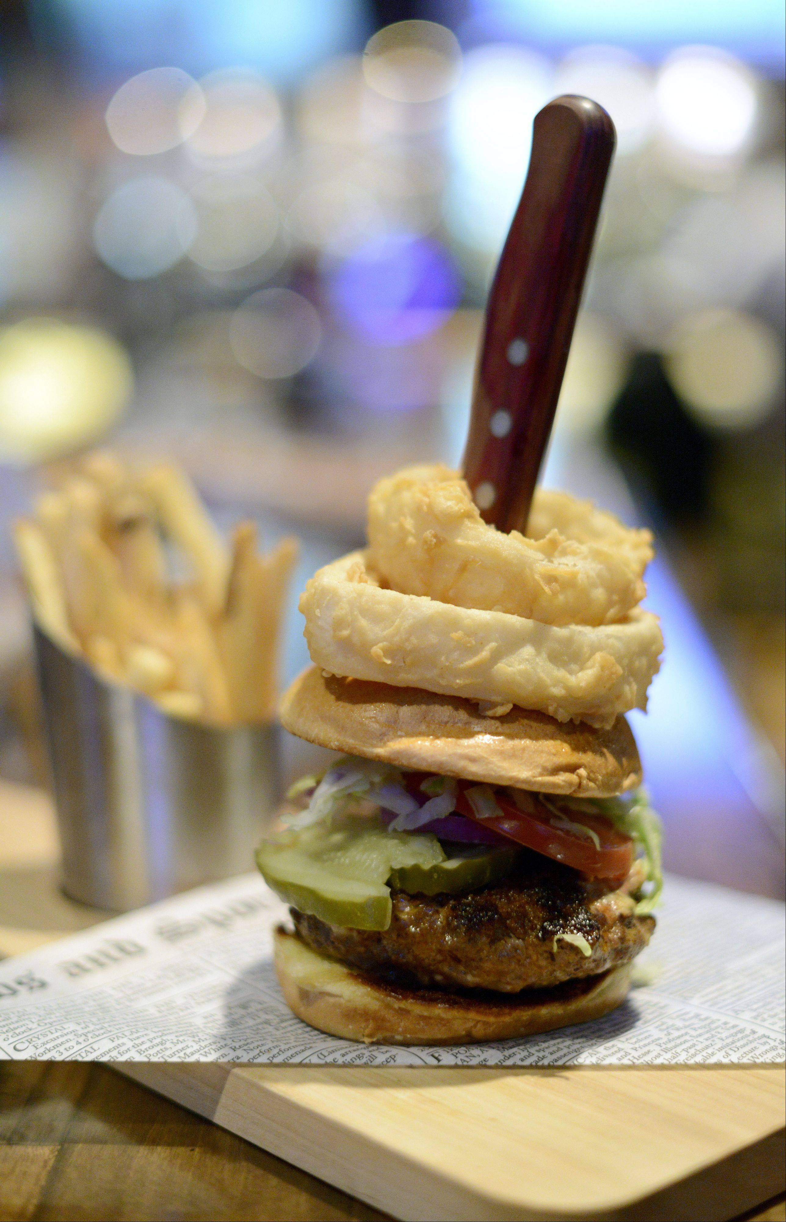 Fox & Hound's Utimate Burger is made with Angus beef and Chorizo sausage, guacamole, jalape�os and cheese. It's topped with spicy mayonnaise, lettuce, tomato, red onions and pickles, and then served with two onion rings.