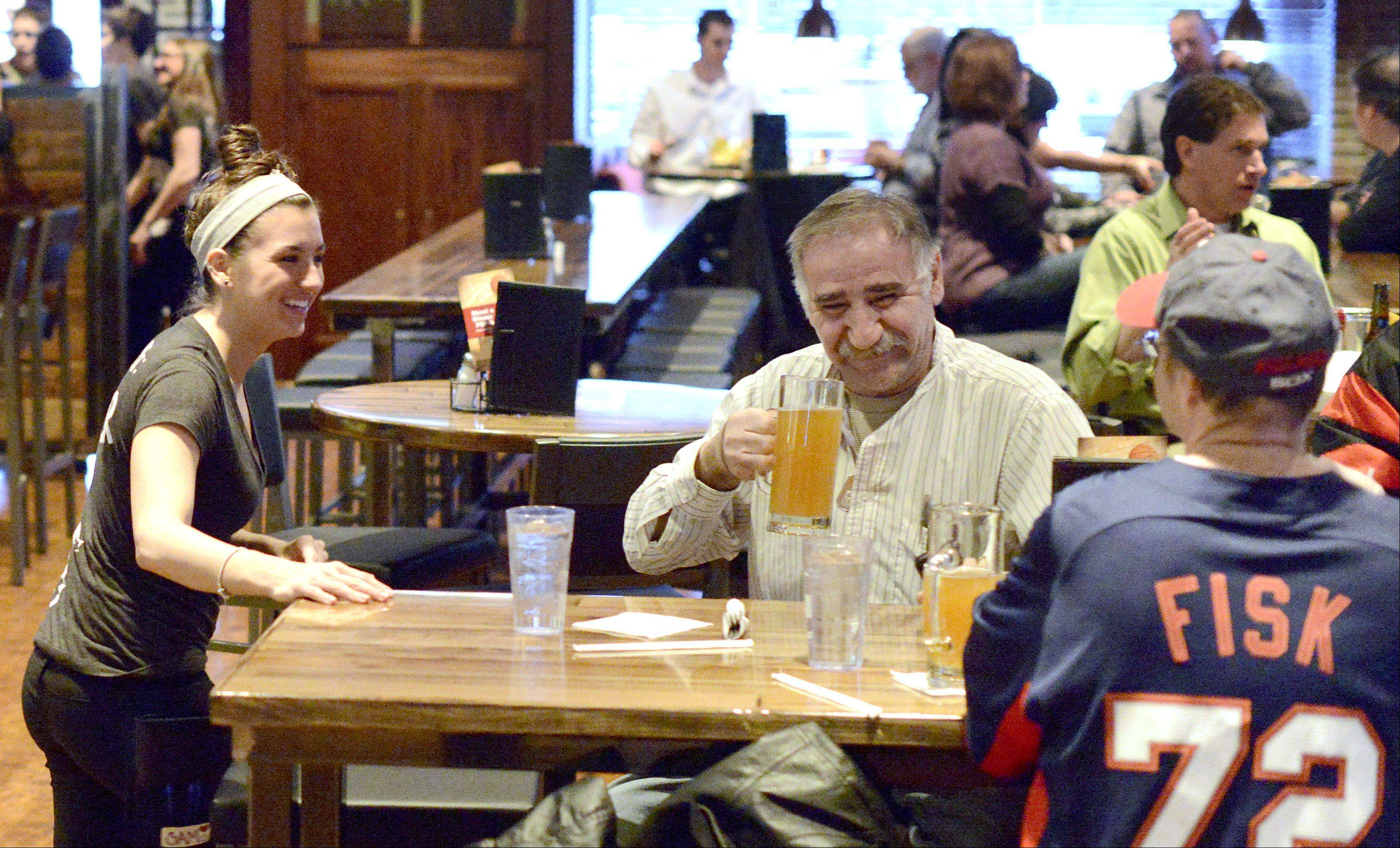 Patrons gather at long tables to drink beer and catch a game at Fox & Hound Sports Tavern in Arlington Heights.