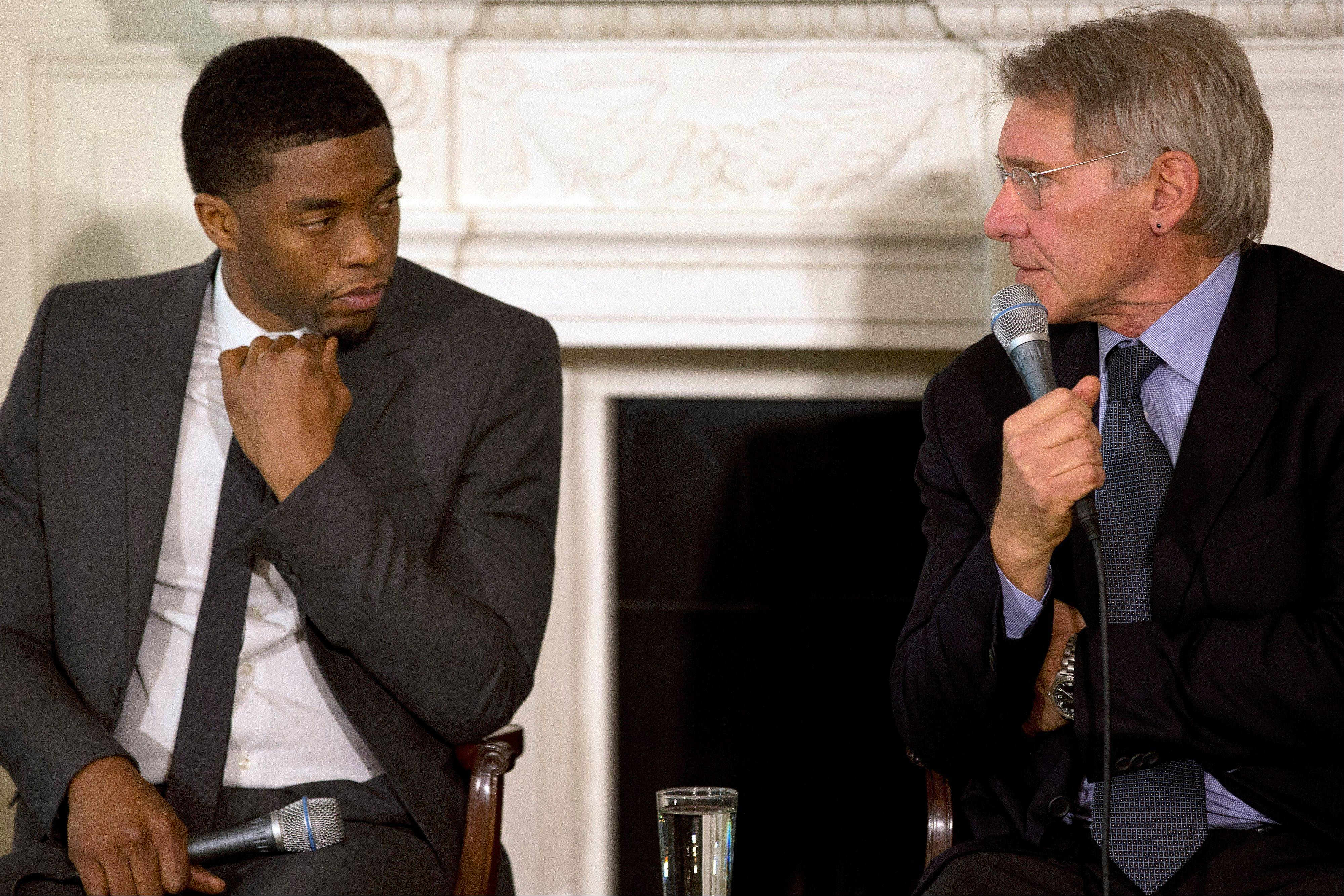 "Actor Chadwick Boseman, left, listens as actor Harrison Ford speaks on a panel of the cast and crew of the movie ""42,"" at the White House. Boseman plays the role of baseball great Jackie Robinson in the movie, and Ford plays Dodgers general manager Branch Rickey."