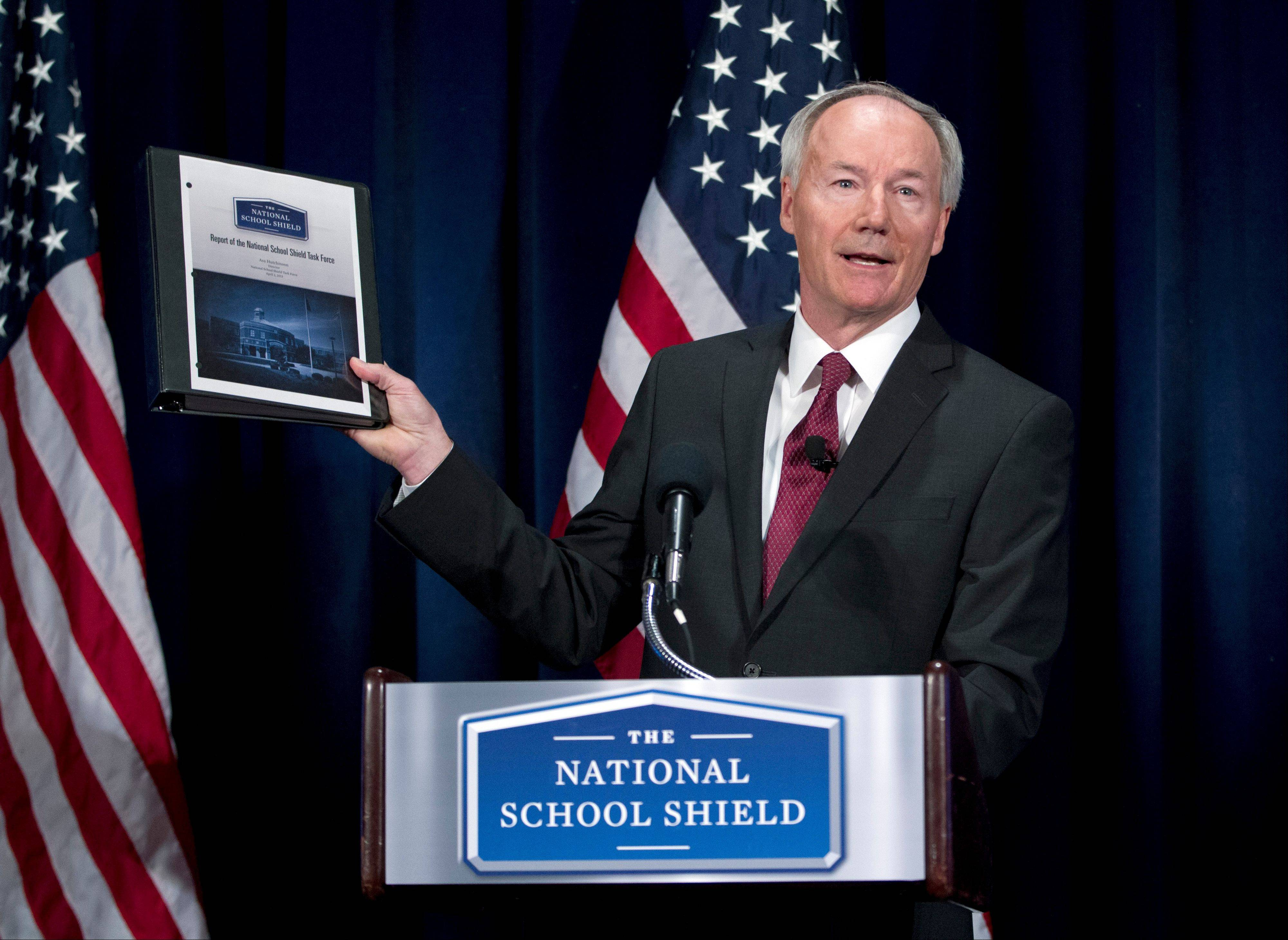 National School Shield Task Force Director, former Arkansas Rep. Asa Hutchinson, holds a copy of group's study during a news conference at National Press Club in Washington Tuesday. The National Rifle Association's study recommends schools across the nation each train and arm at least one staff member.