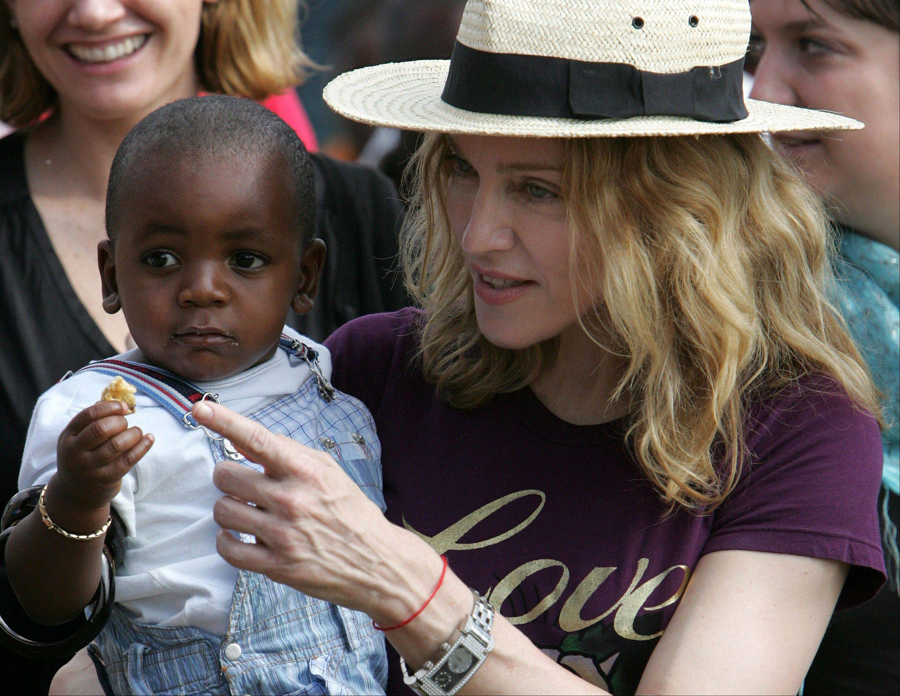 Madonna, seen here carrying her Malawian adopted son David Banda in 2007, helped fund several community schools to benefit more Malawians and was in the country Tuesday to celebrate their opening.