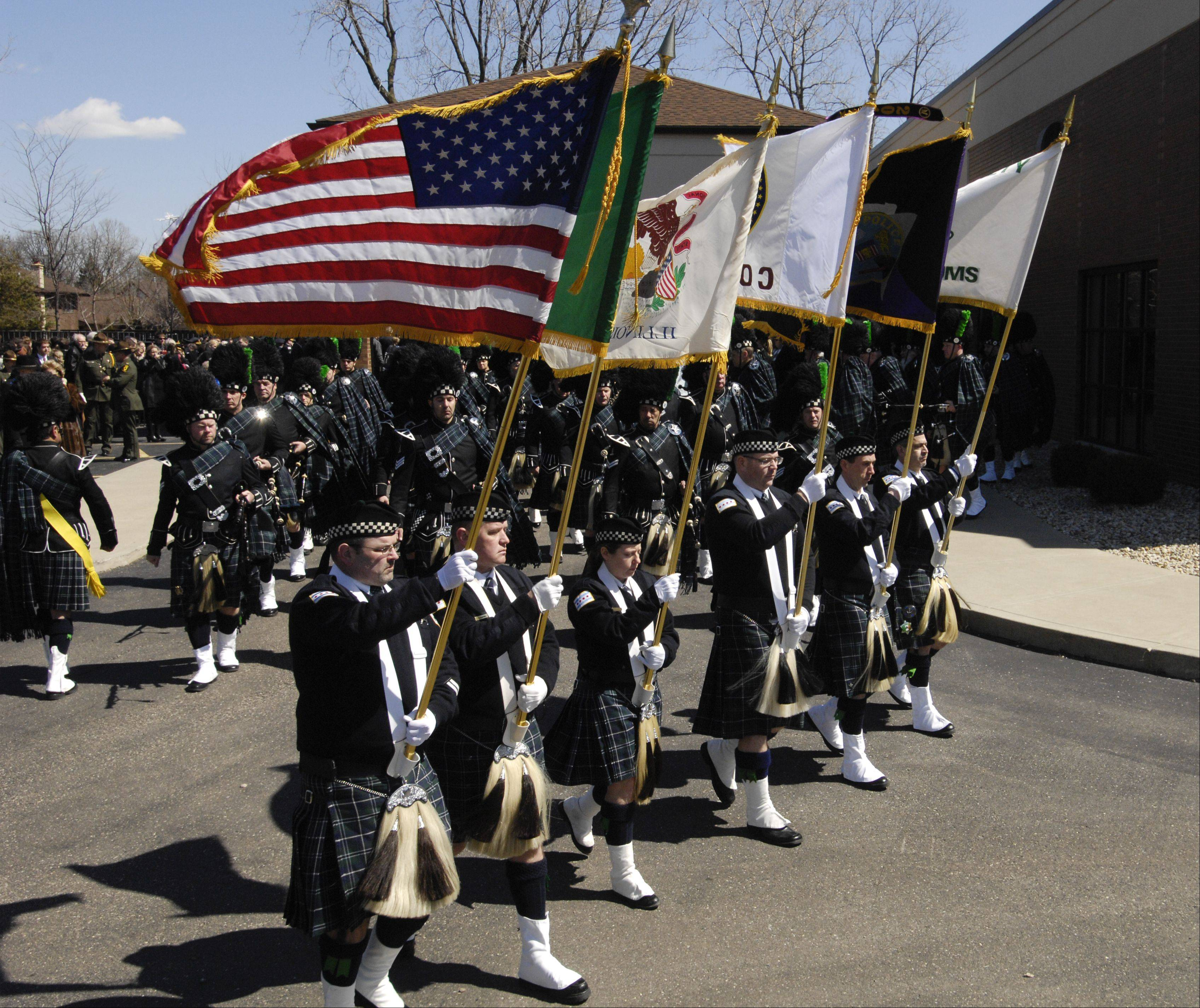 The bagpipe corps marches out after the funeral service for Illinois State Police Trooper James Sauter at Moraine Valley Church in Palos Heights Tuesday morning.