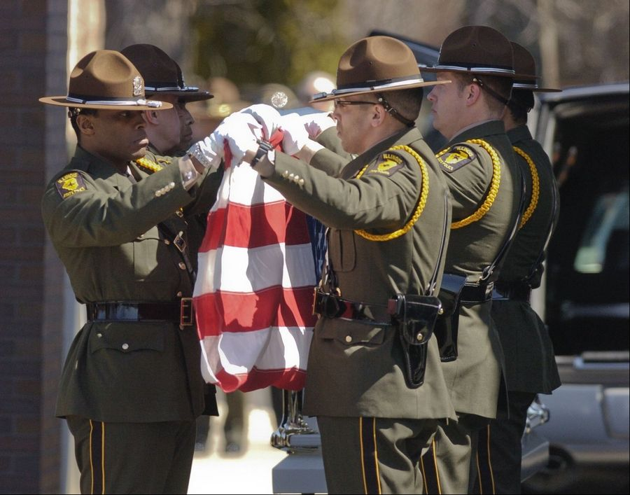 Fellow troopers fold the American flag from the casket of fallen Illinois State Police Trooper James Sauter at Moraine Valley Church in Palos Heights Tuesday morning.