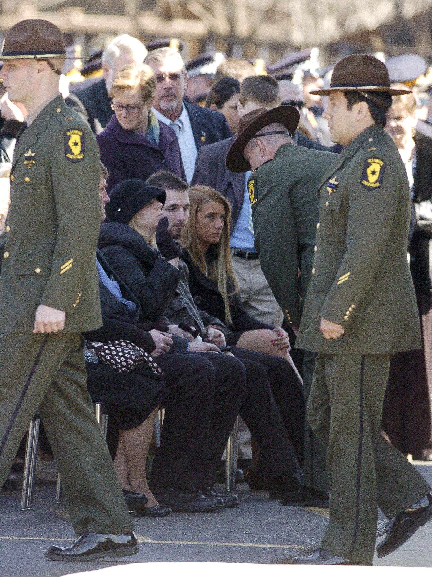 The family of Illinois State Police Trooper James Sauter watches as fellow troopers form ranks during the funeral service at Moraine Valley Church in Palos Heights Tuesday morning.