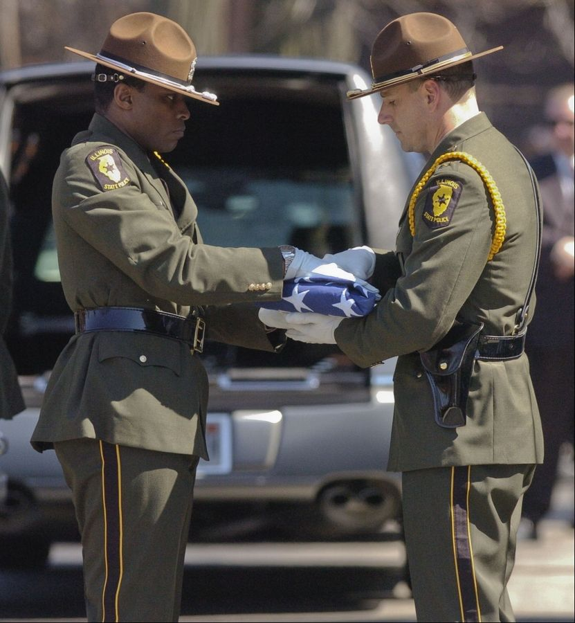 The folded American flag from the casket of fallen Illinois State Police Trooper James Sauter is handed off during the funeral ceremony at Moraine Valley Church in Palos Heights Tuesday morning.