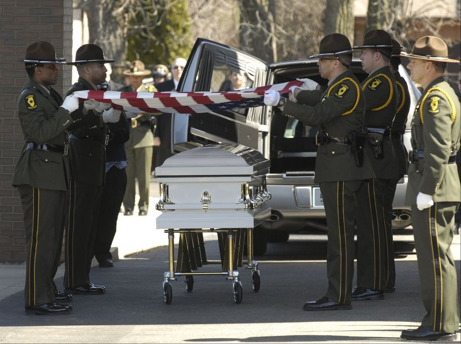 Fellow troopers fold the American Flag from the casket of fallen Illinois State Police Trooper James Sauter during the funeral service at Moraine Valley Church in Palos Heights Tuesday morning.