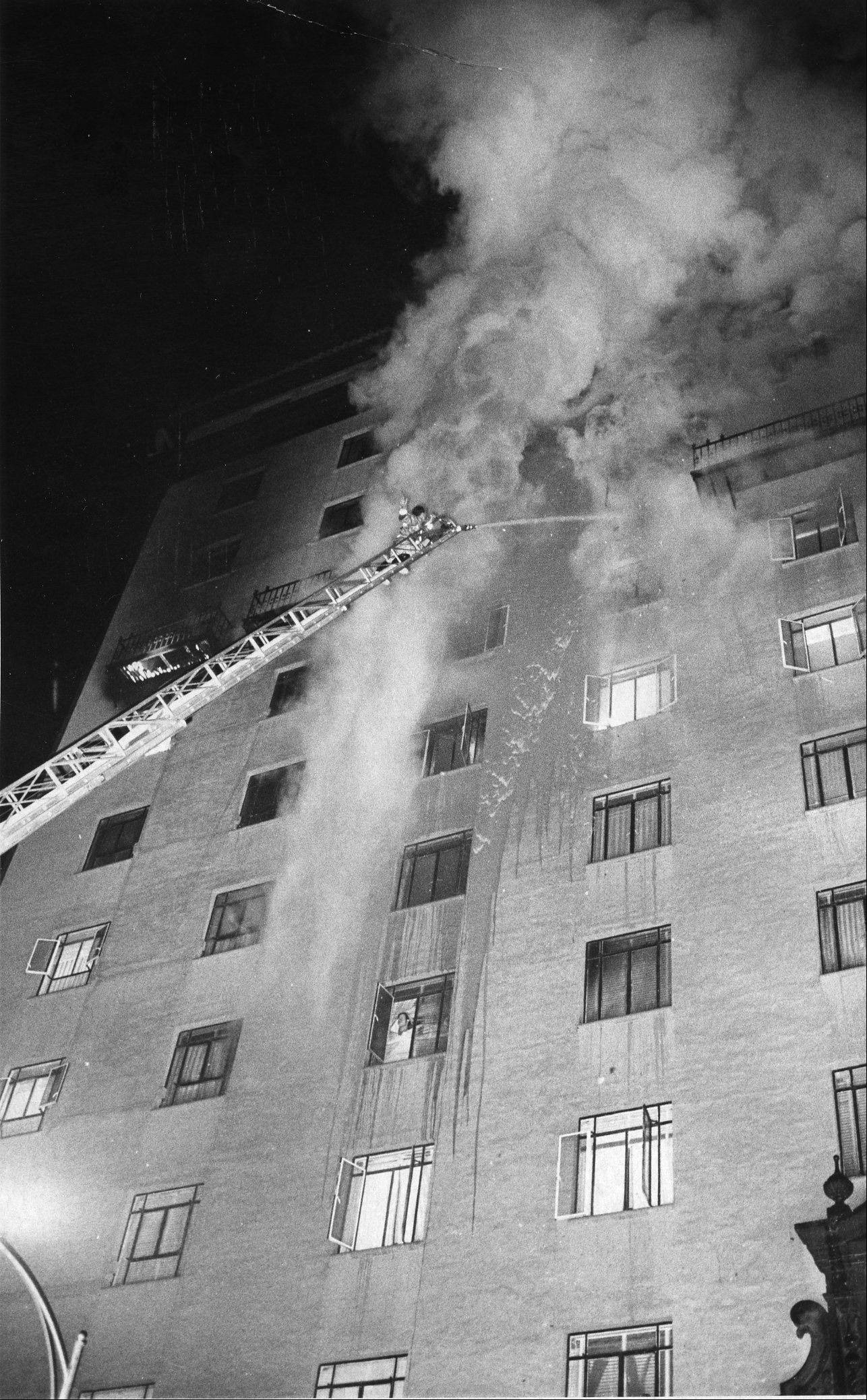 In a Dec. 20, 1970 photo Tucson, Ariz., firefighters apply a steady stream of water during the Pioneer International Hotel fire , that resulted in 29 deaths.