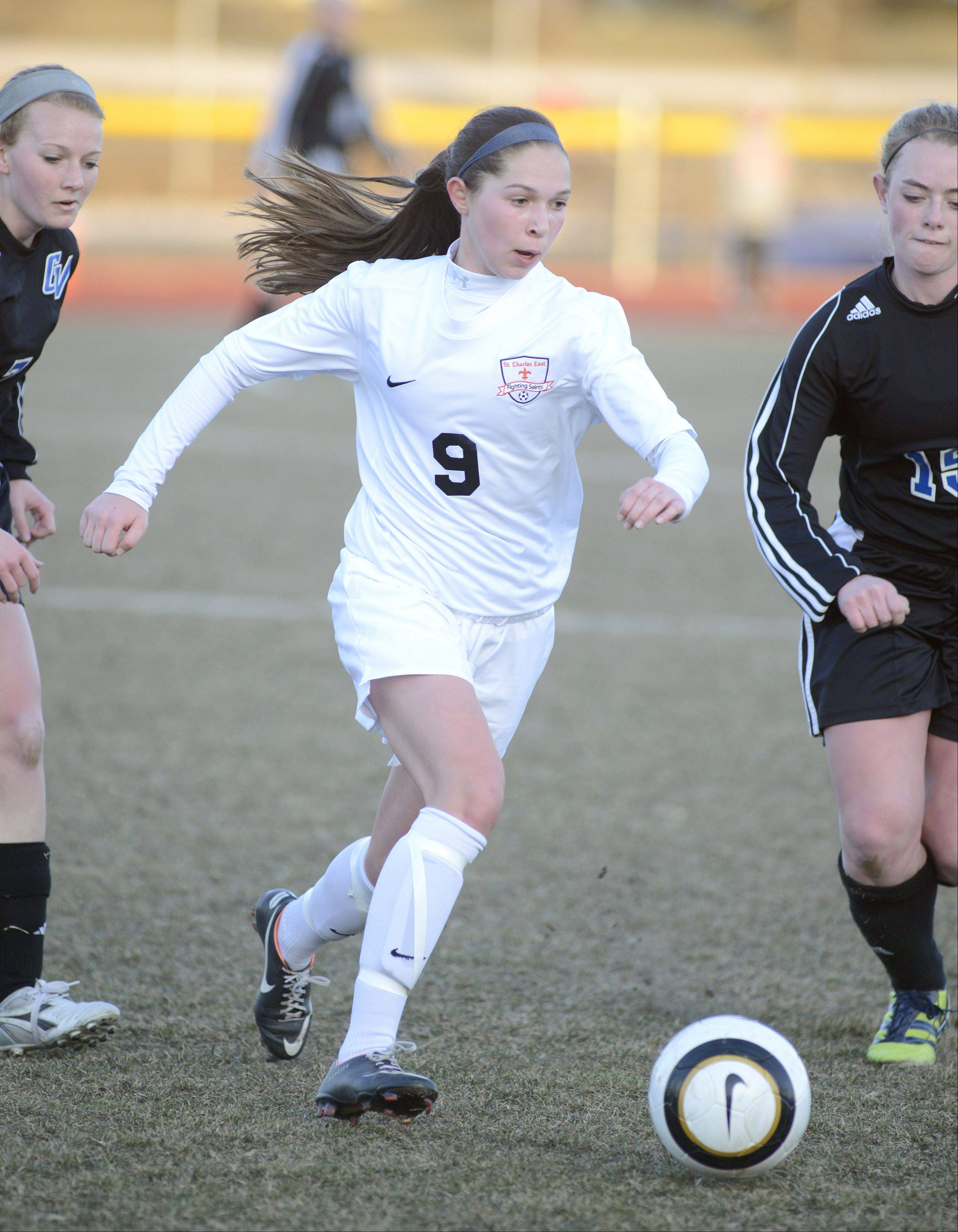 St. Charles East's Darcy Cunningham drives the ball past Geneva's Annie Waldoch, right, in the first half on Tuesday, April 2.