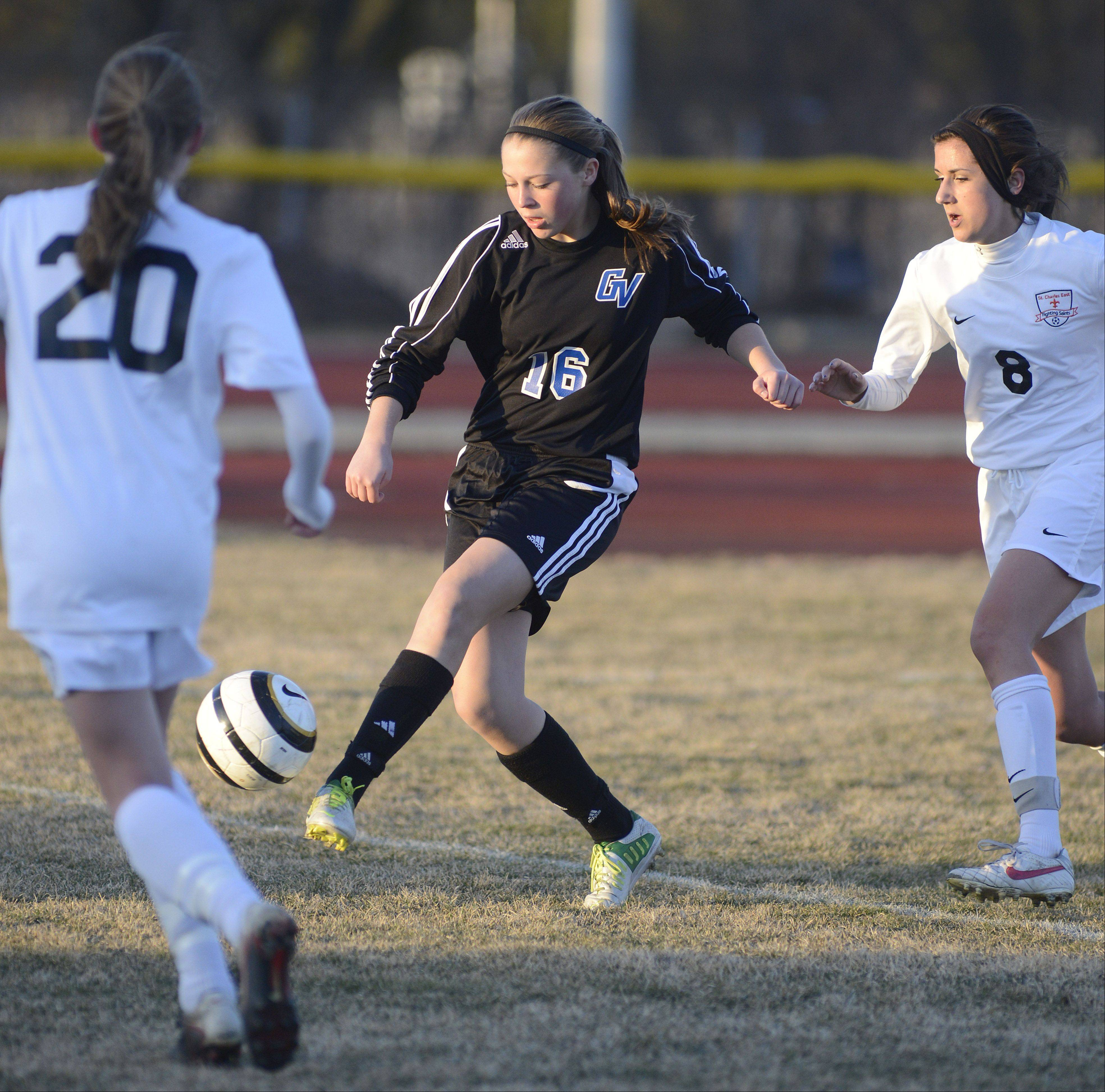 Geneva's Maureen Kozlow attempts to get the ball past St. Charles East's Sam Lombardo, left, and Morgan Settle in the first half on Tuesday, April 2.