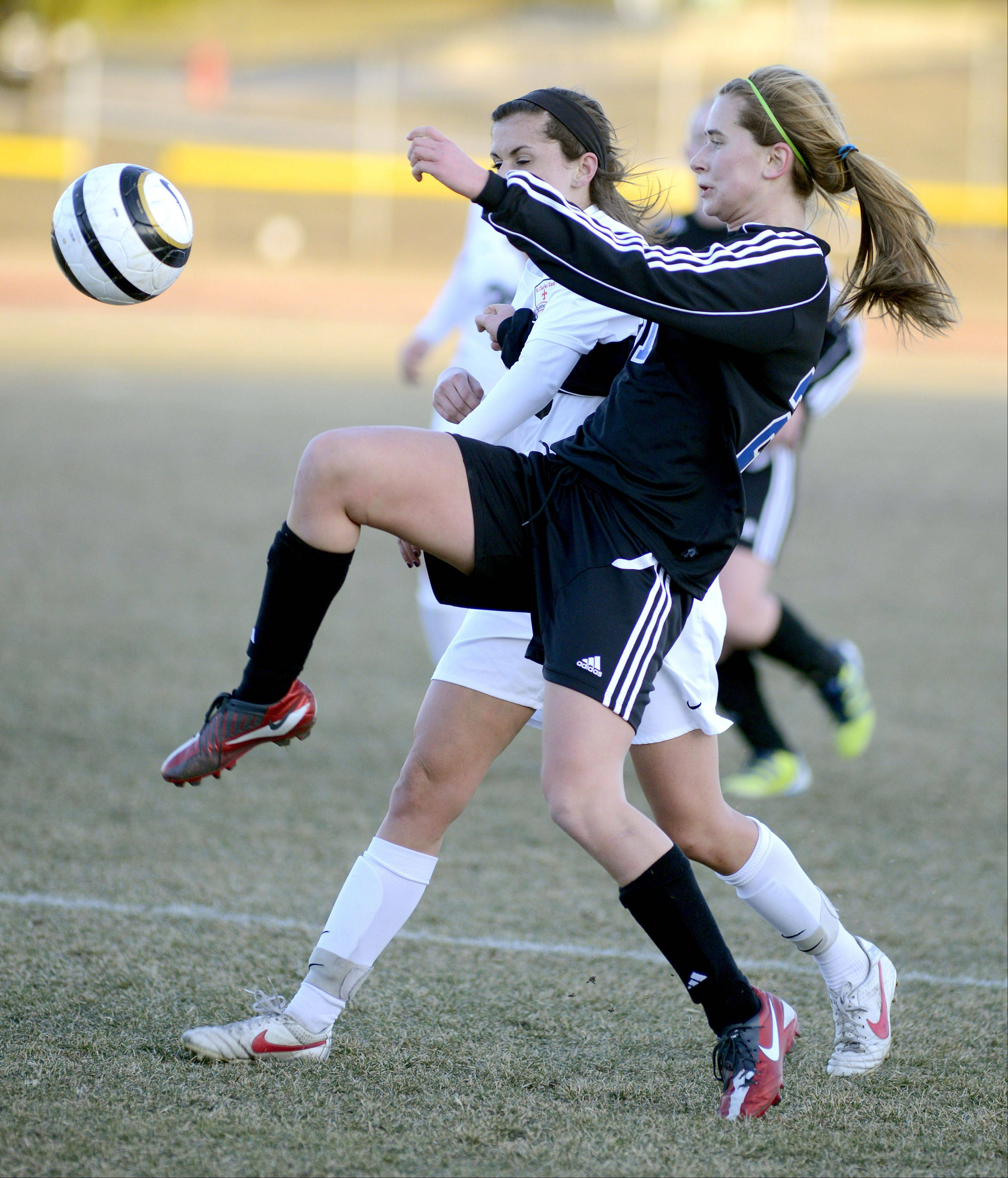 St. Charles East's Morgan Settle and Geneva's Mary Landry battle for the ball in the first half on Tuesday, April 2.
