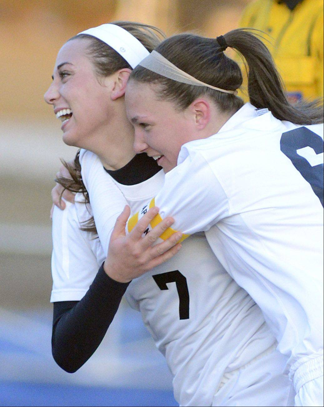 St. Charles East's Allie Arvizu, left, is congratulated by teammate and captain Carly Pottle moments after scoring a goal over Geneva in the first half on Tuesday, April 2.