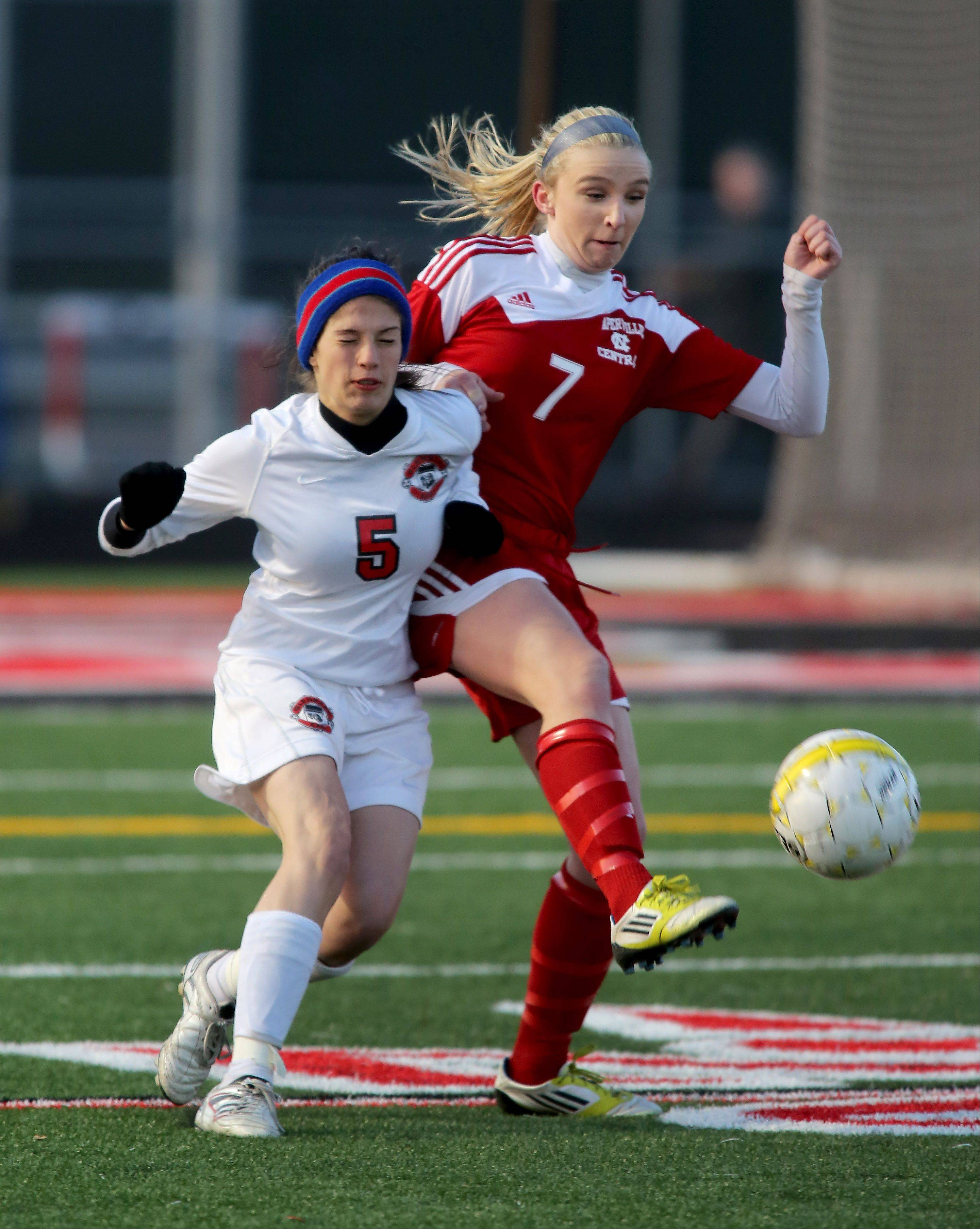 Kellie Brooks of Naperville Central, right, passes the ball away from Nicole Alfaro of Glenbard East during girls soccer on Tuesday in Lombard.