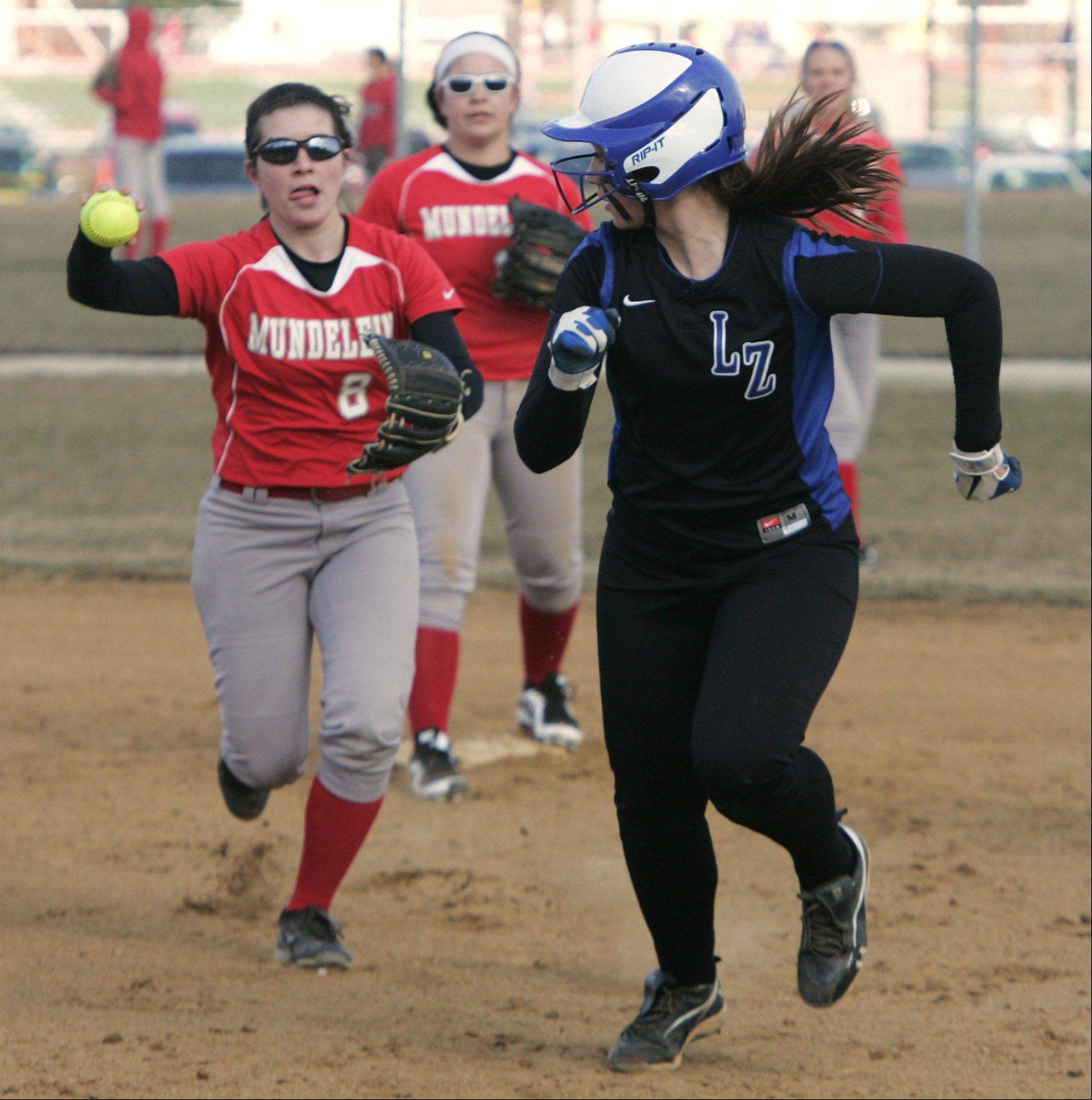 Lake Zurich runner Mallory Parsons gets caught in a rundown between second base and first base by Mundelein shortstop Maddie Zazas in the first inningon Tuesday. Parsons made it safely to second base.