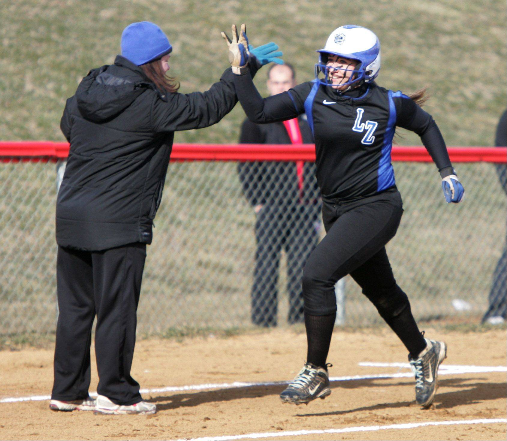 Lake Zurich hitter Maria Schroeder is congratulated as she rounds third base after hitting a 3-run homer in the first inning Tuesday at Mundelein.
