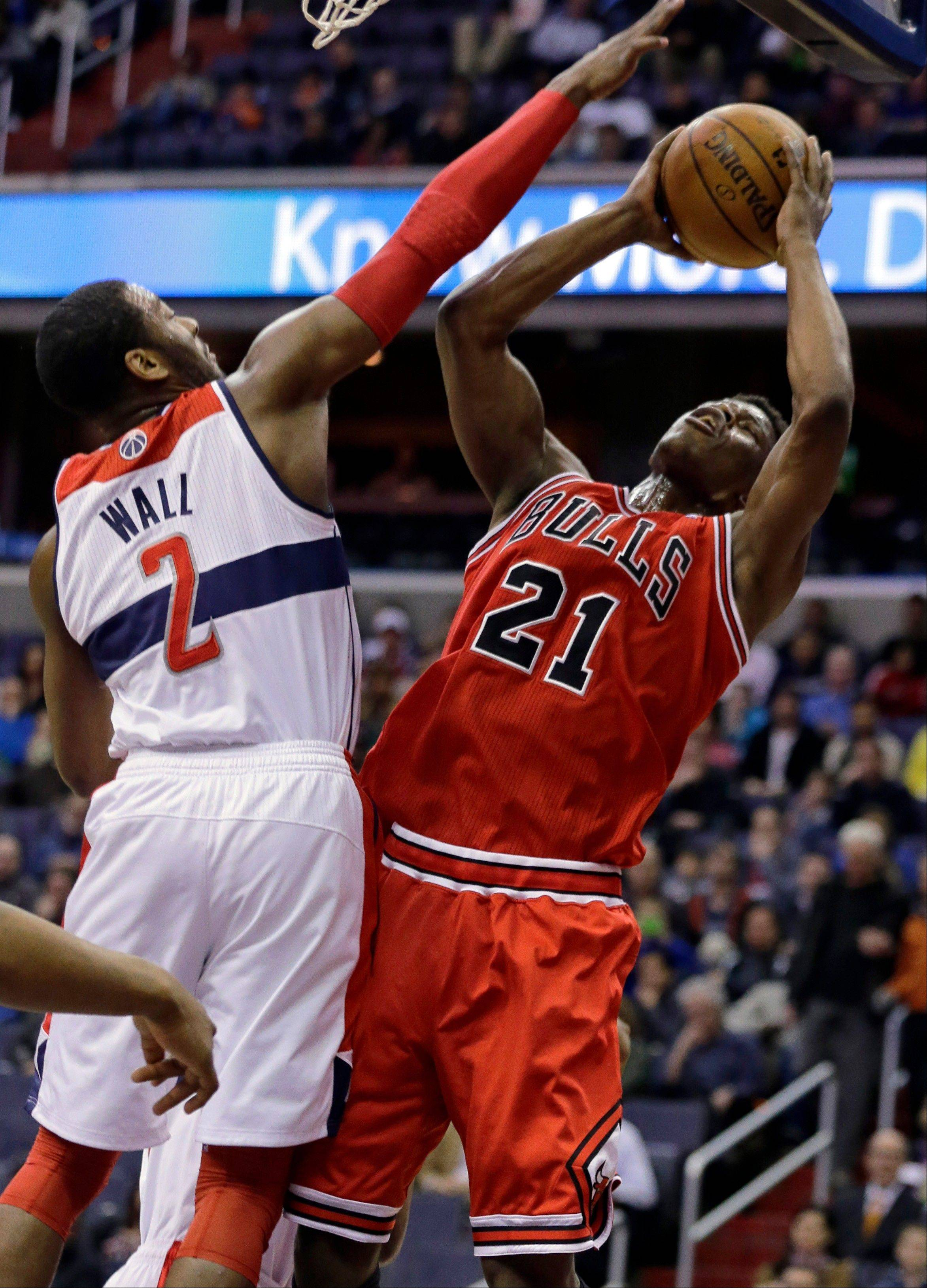 Chicago Bulls forward Jimmy Butler (21) shoots in front of Washington Wizards guard John Wall (2) in the first half of an NBA basketball game Tuesday, April 2, 2013, in Washington.
