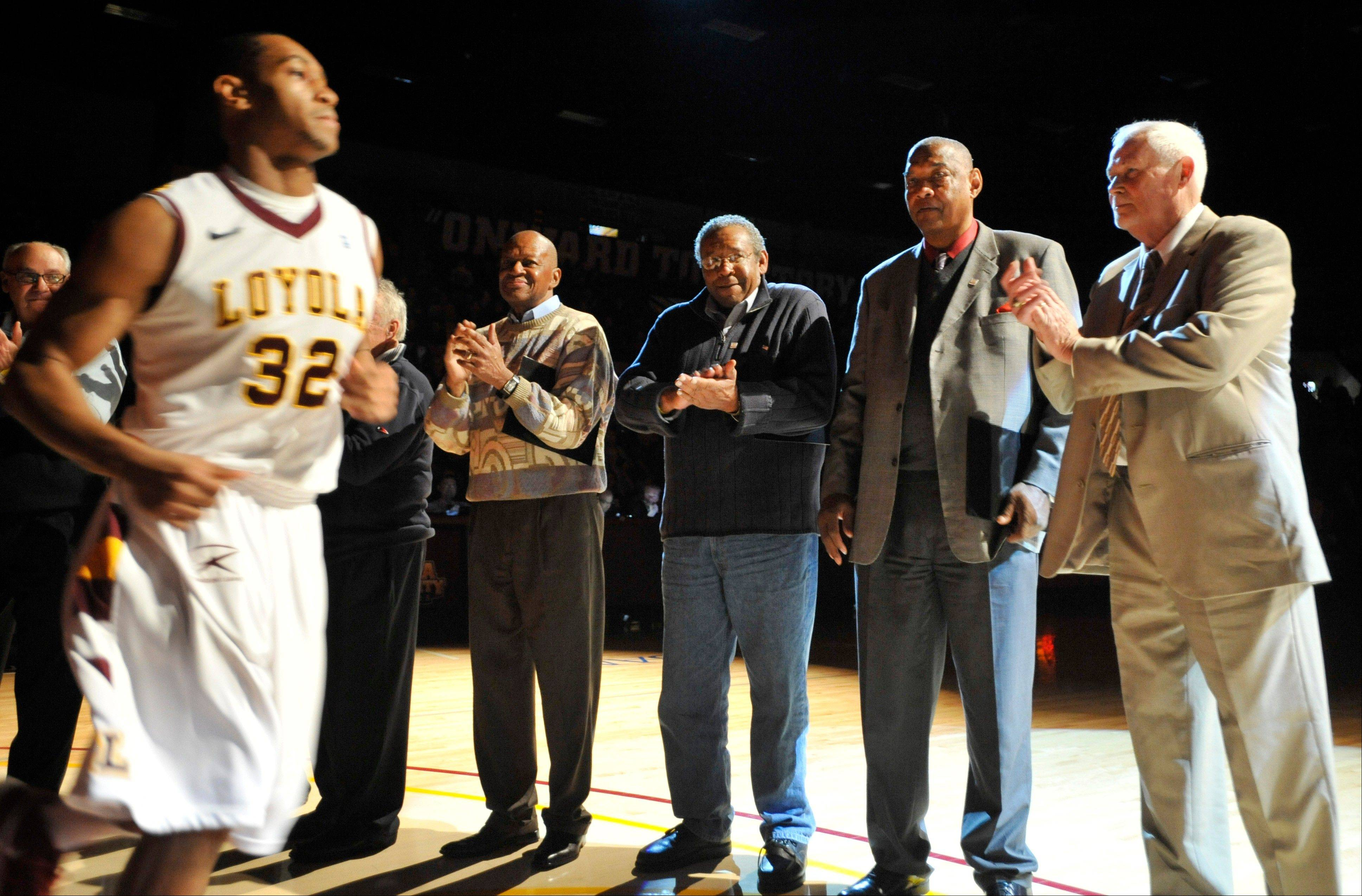 Members of the 1963 Loyola NCAA men's basketball championship team cheer on current Loyola player Christian Thomas (32) as he is announced before game between Loyola and Mississippi State last December. The 1963 Loyola team is being inducted into the National Collegiate Basketball Hall of Fame.