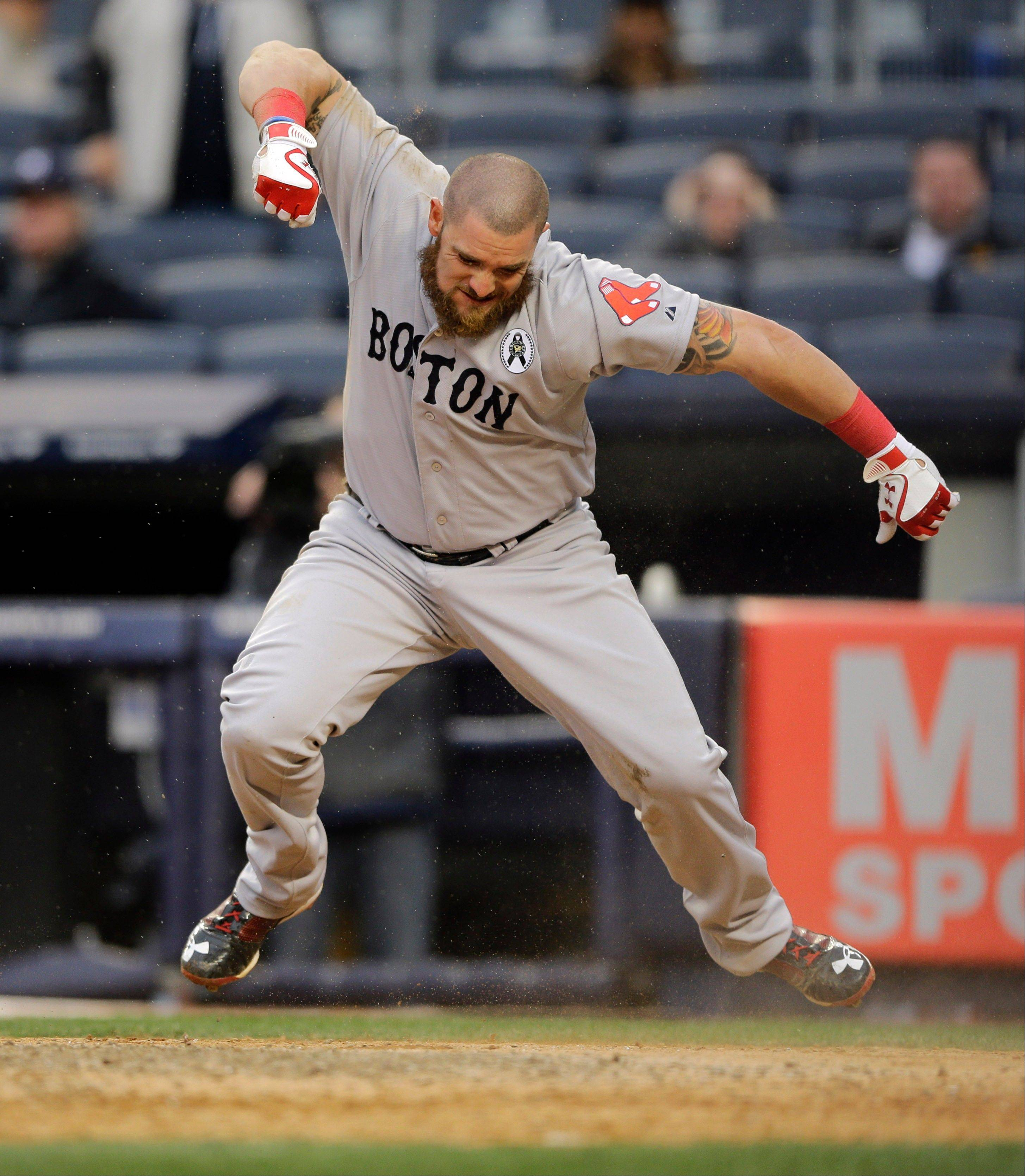 Boston's Jonny Gomes celebrates after scoring on a two-run single by Jacoby Ellsbury during the ninth inning Monday in New York.
