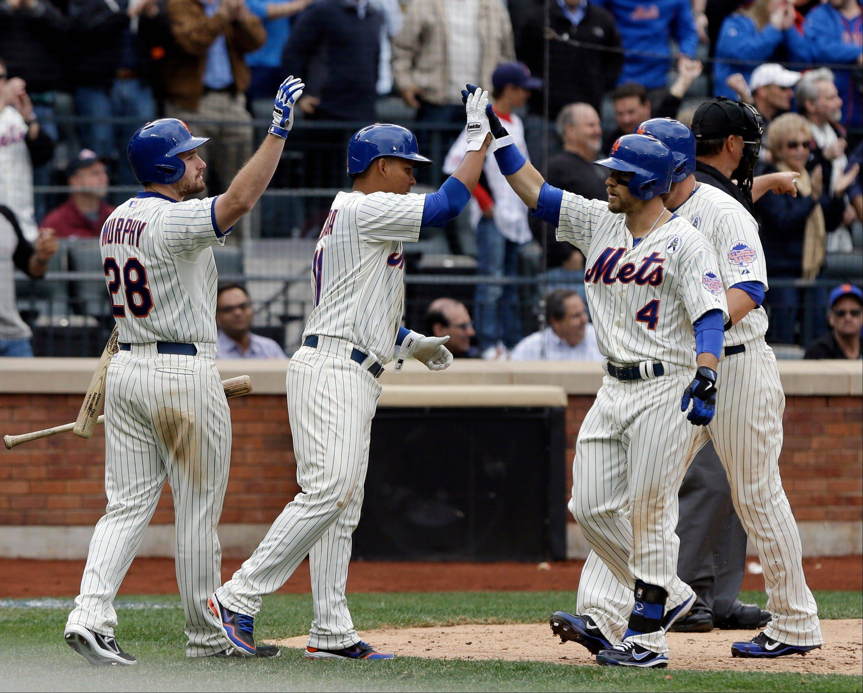 The Mets' Collin Cowgill (4) celebrates with teammates Daniel Murphy (28), Ruben Tejada, second from left, and John Buck, right, after hitting a grand slam against the Padres in the seventh inning Monday at home