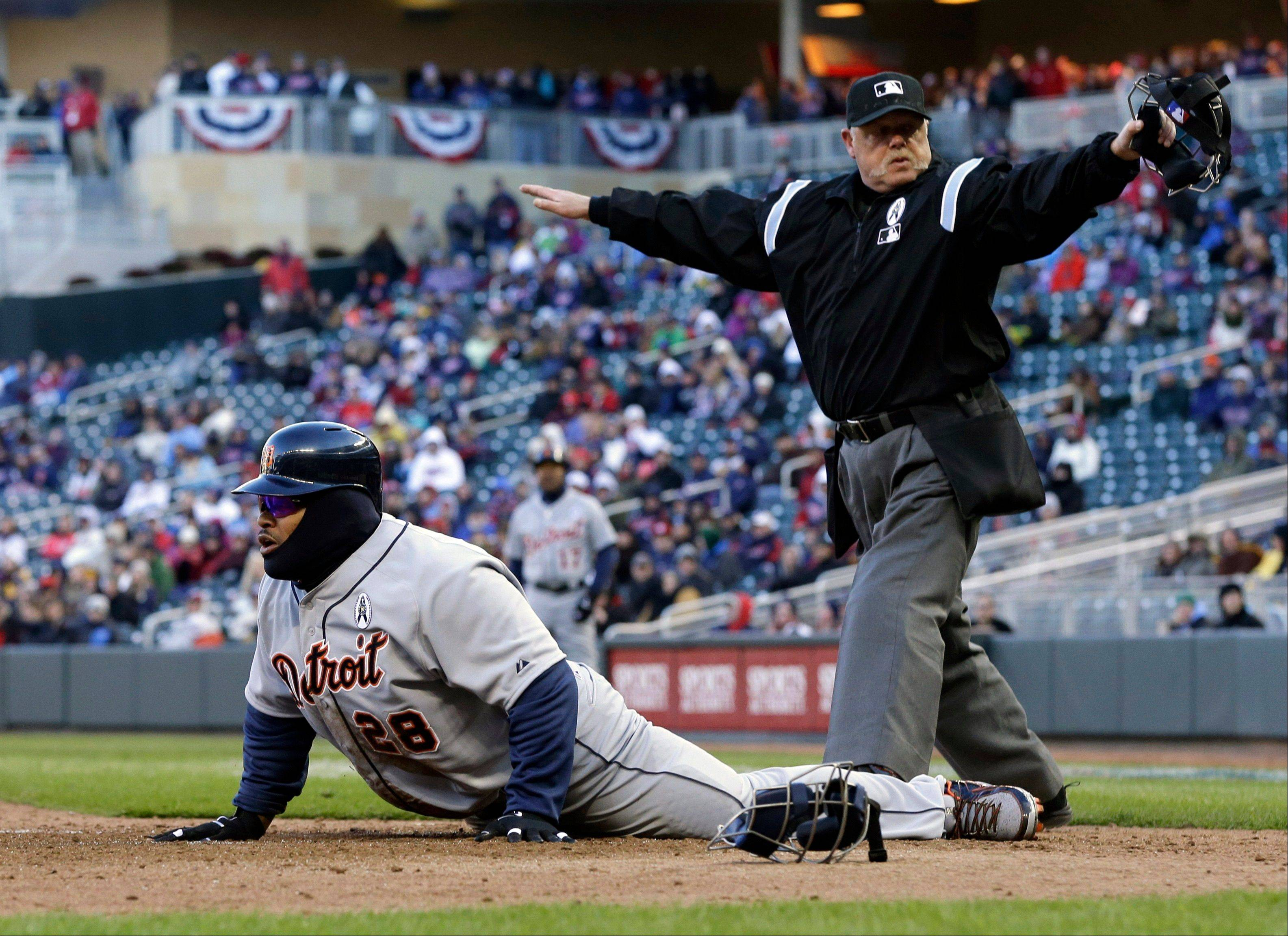 Plate umpire Jim Joyce signals Detroit Tigers' Prince Fielder safe as he scores on a wild pitch by Minnesota Twins pitcher Josh Roenicke in the eighth inning Monday.