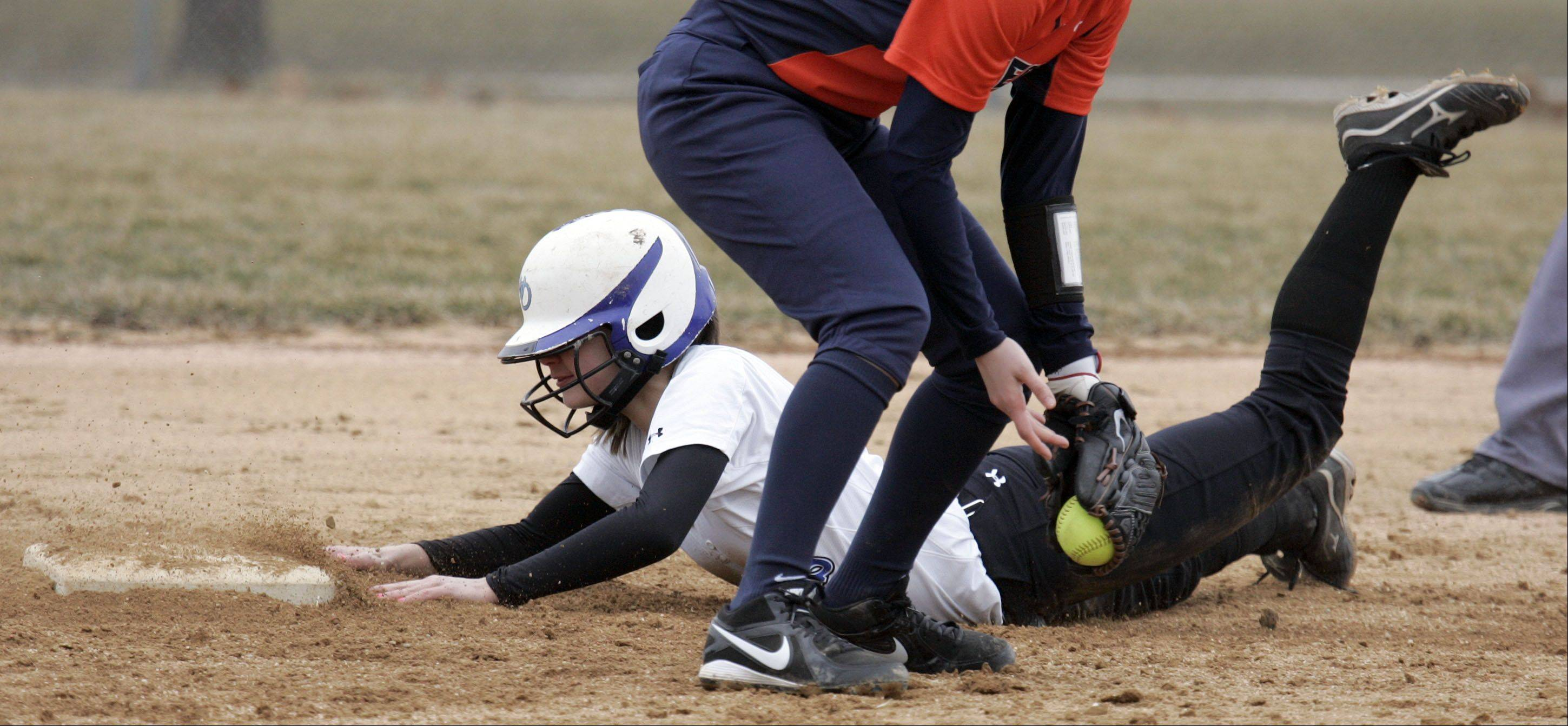 Geneva's Anna Geary, 7, slides safely under the tag of Oswego's Savanna Brady, 16, at second base during softball action Wednesday in Geneva.