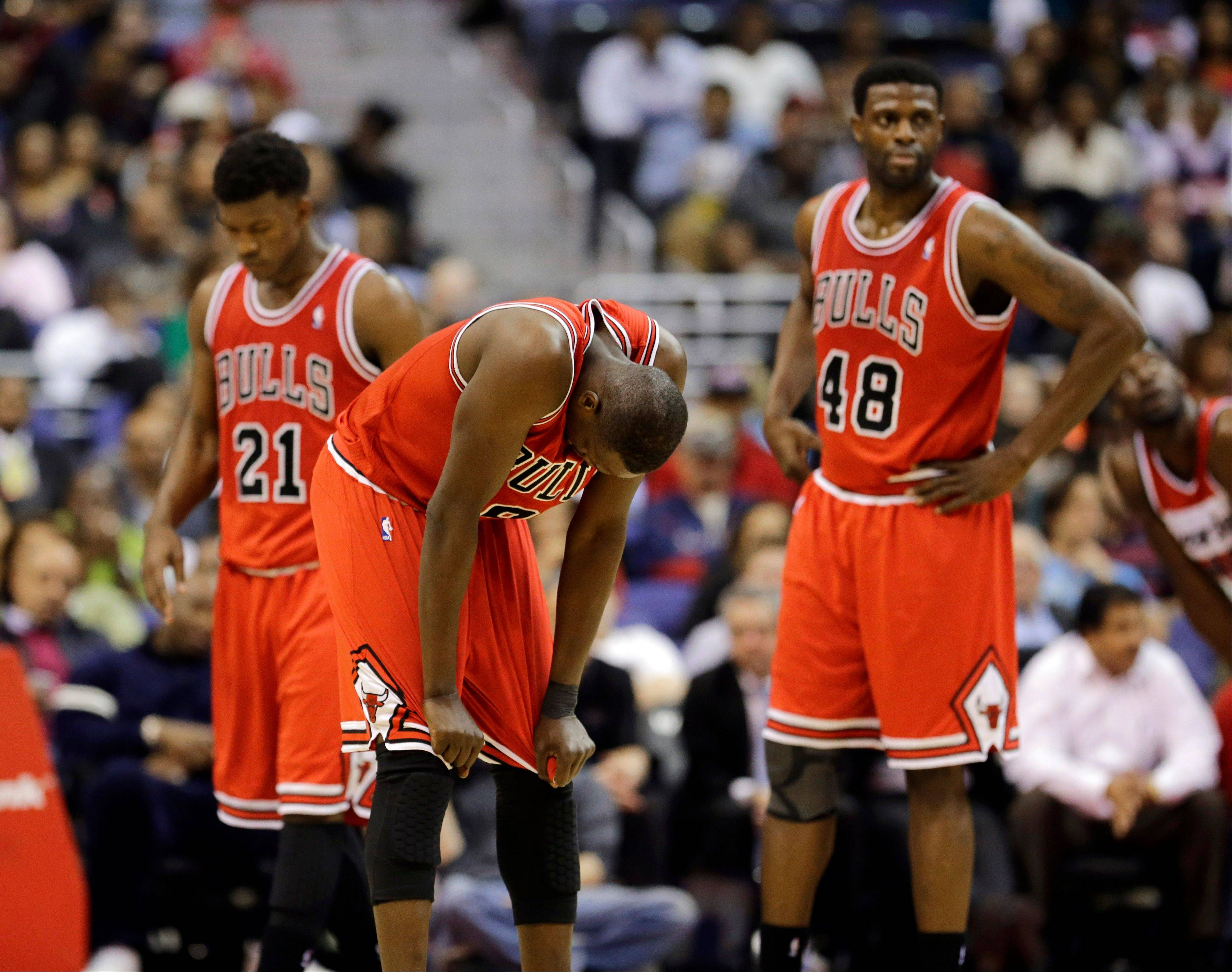Jimmy Butler (21), forward Luol Deng (9), from Sudan, and center Nazr Mohammed (48) pause on the court during a break in the action in the second half of the Bulls' loss to Washington on Tuesday.