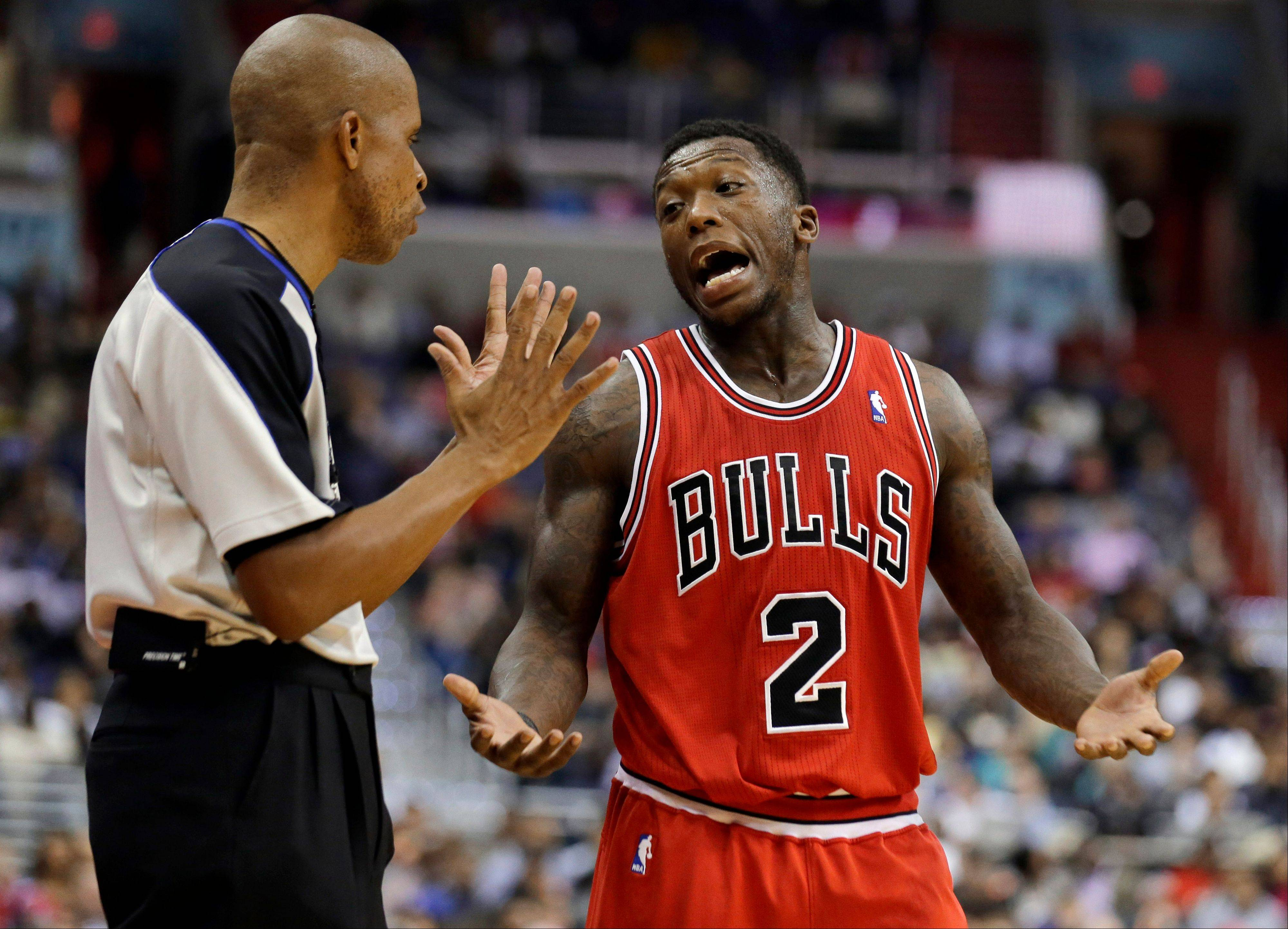 Referee Sean Corbin listens to Chicago Bulls guard Nate Robinson (2) in the second half of the Bulls' NBA basketball game against the Washington Wizards on Tuesday, April 2, 2013, in Washington. The Wizards won 90-86.