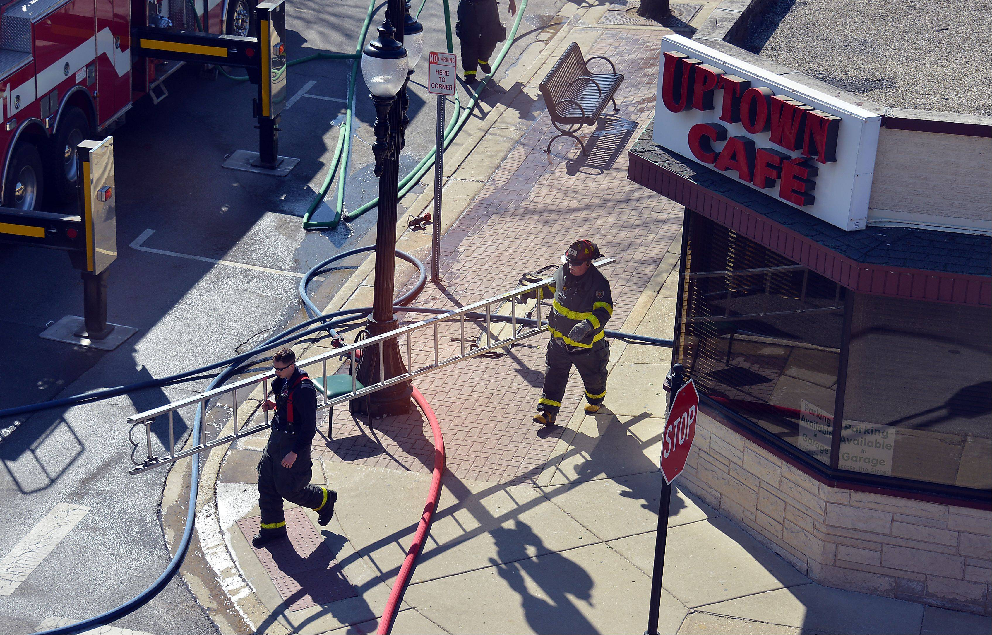 Arlington Heights firefighters carry ladders to access the roof at the Uptown Cafe restaurant after a fire started there in the early afternoon on Wednesday.