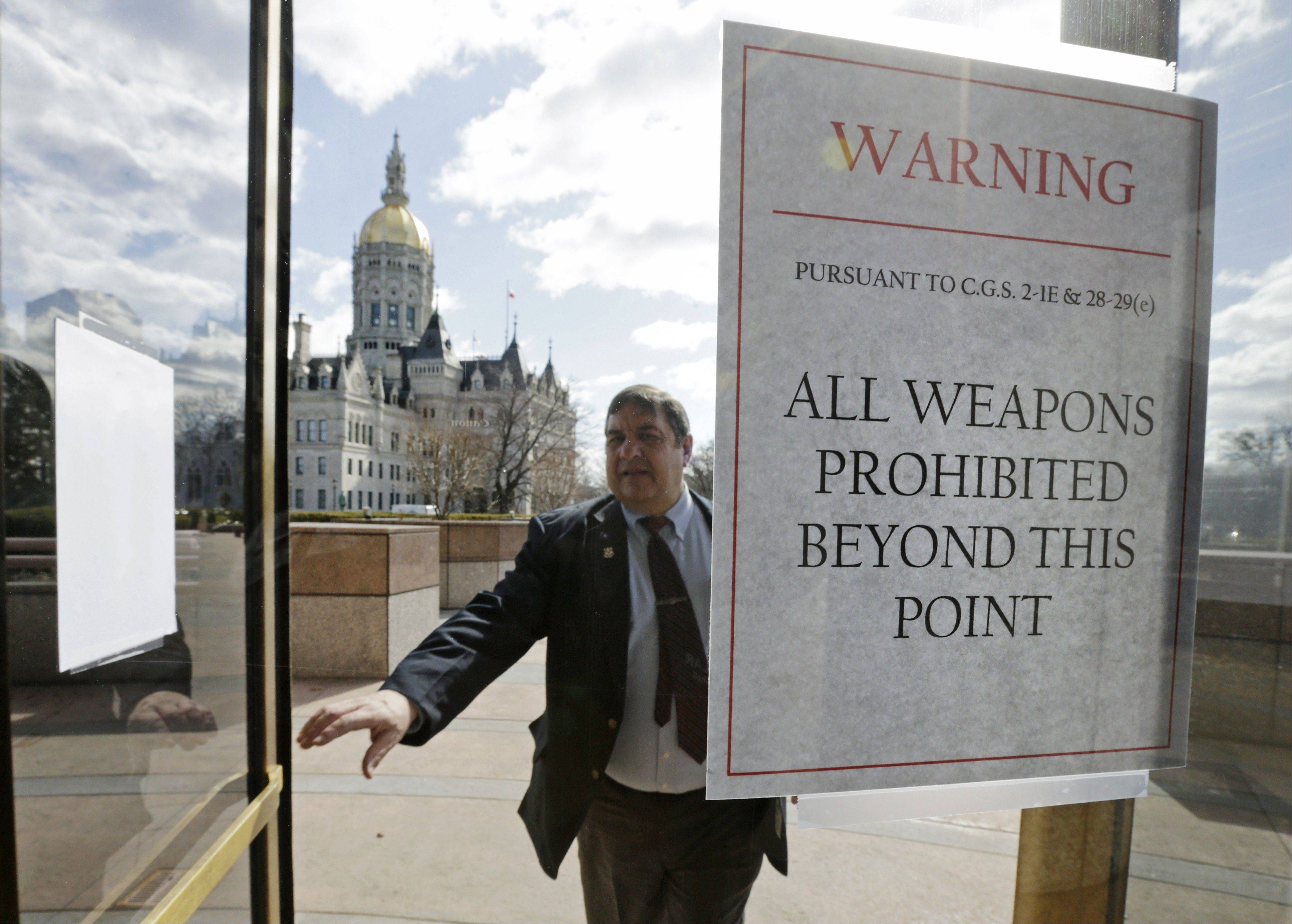 A Capitol security passes a sign warning not to bring weapons on to the grounds at the Capitol in Hartford, Conn., Wednesday. Hundreds of gun rights advocates gathered ahead of a vote in the state Senate on proposed gun-control legislation, which passed.