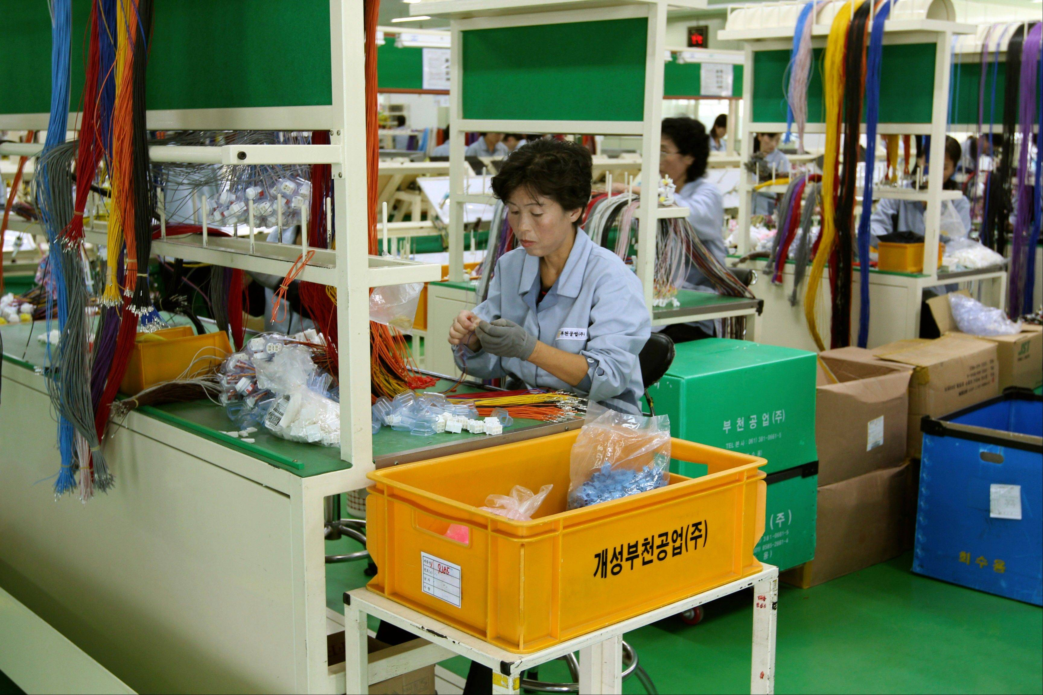 In this September 2012 photo, a North Korean worker handles wires at a South Korean-run factory inside the Kaesong industrial complex in Kaesong, North Korea. On Wednesday, April 3, 2013, North Korea refused entry to South Koreans trying to cross the Demilitarized Zone to get to their jobs managing factories in the North Korean city of Kaesong.
