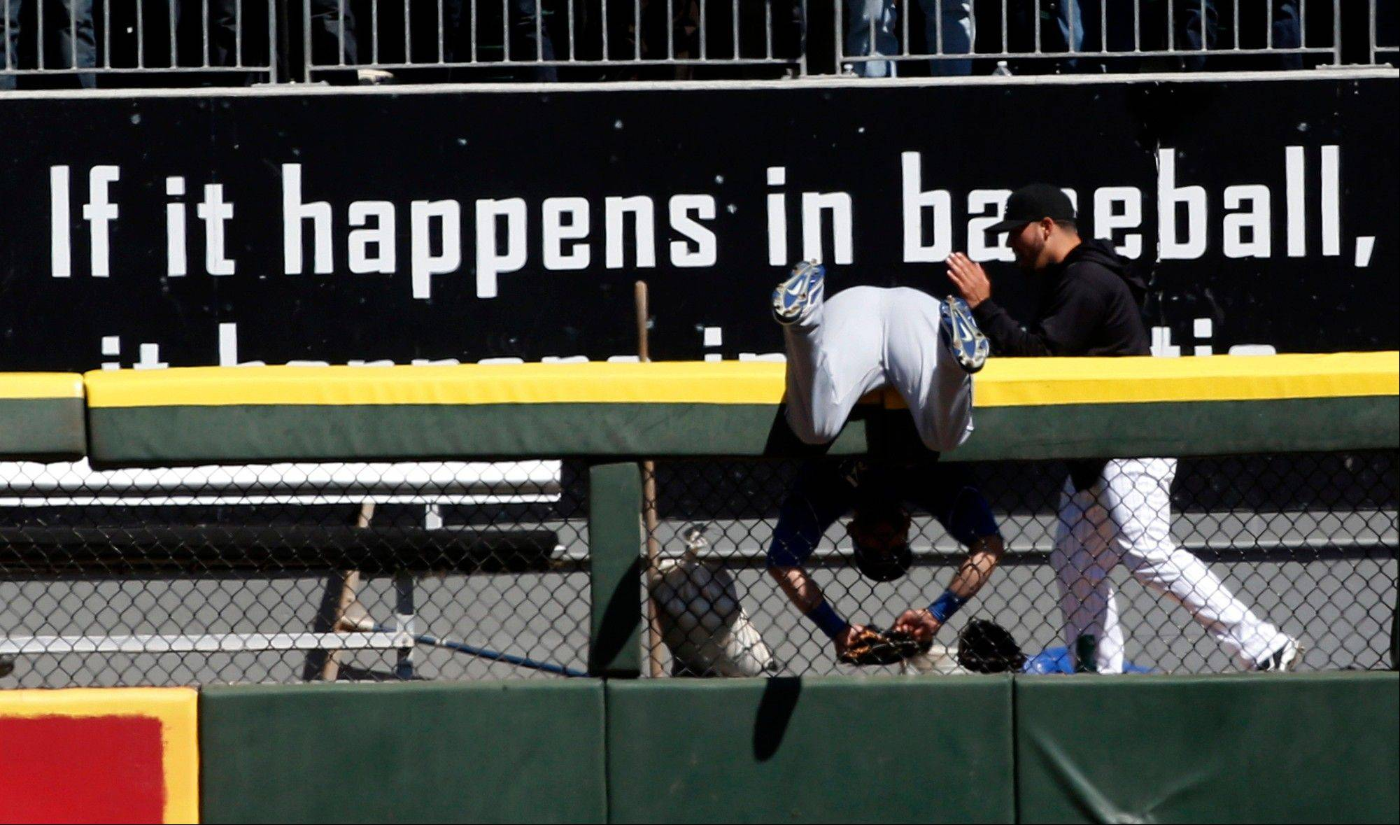 Royals left fielder Alex Gordon hangs over the left field wall after he was unable to catch a 2-run home run by Dayan Viciedo during the fourth inning of the White Sox' victory Wednesday.