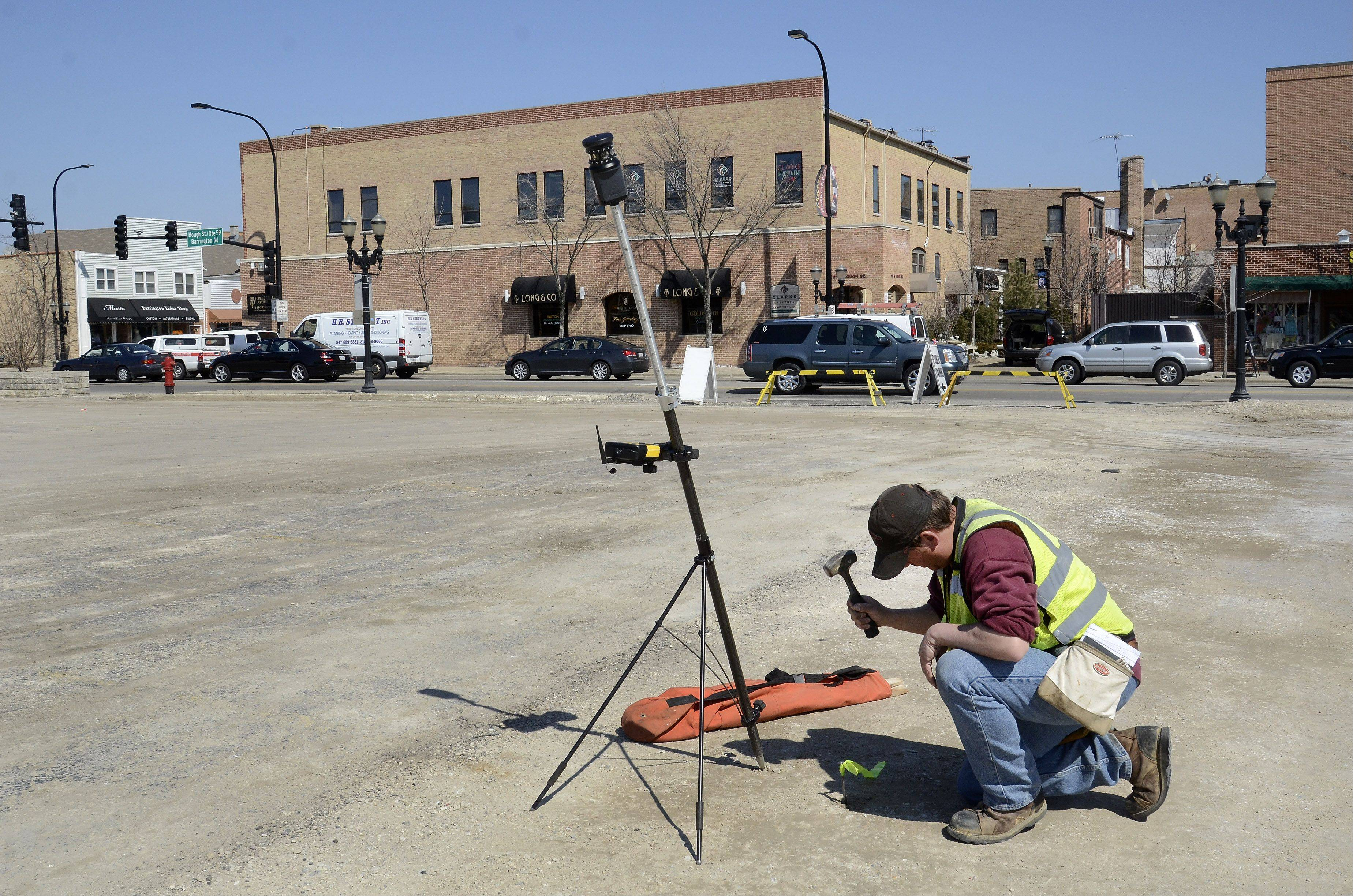 Mark Hamilton of Gewalt Hamilton Associates Inc. stakes out the development site Thursday at the southwest corner of Hough and Main Streets in downtown Barrington.