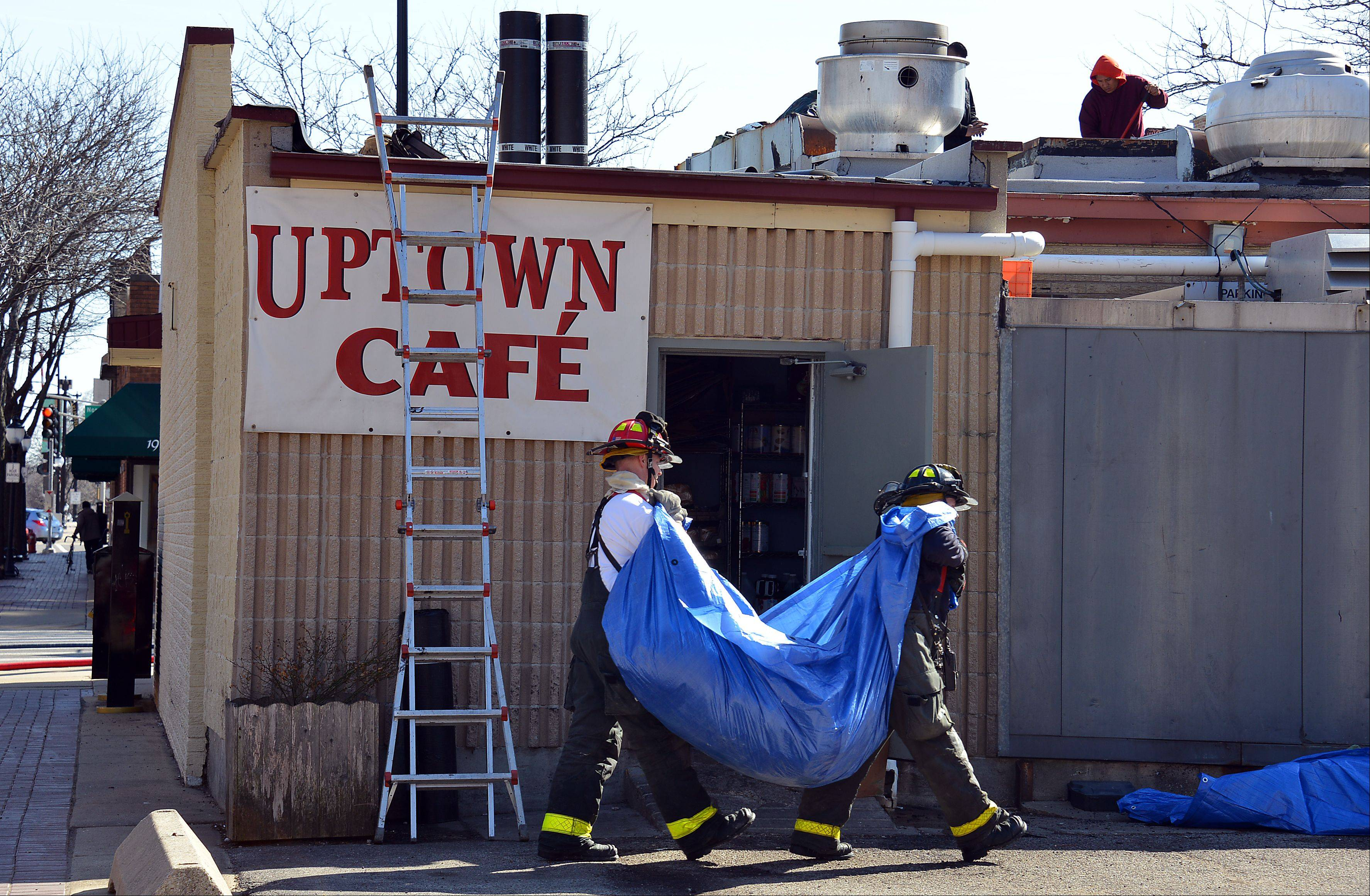 Arlington Heights firefighters carry away charred debris from inside the Uptown Cafe restaurant after a fire started there in the early afternoon on Wednesday.