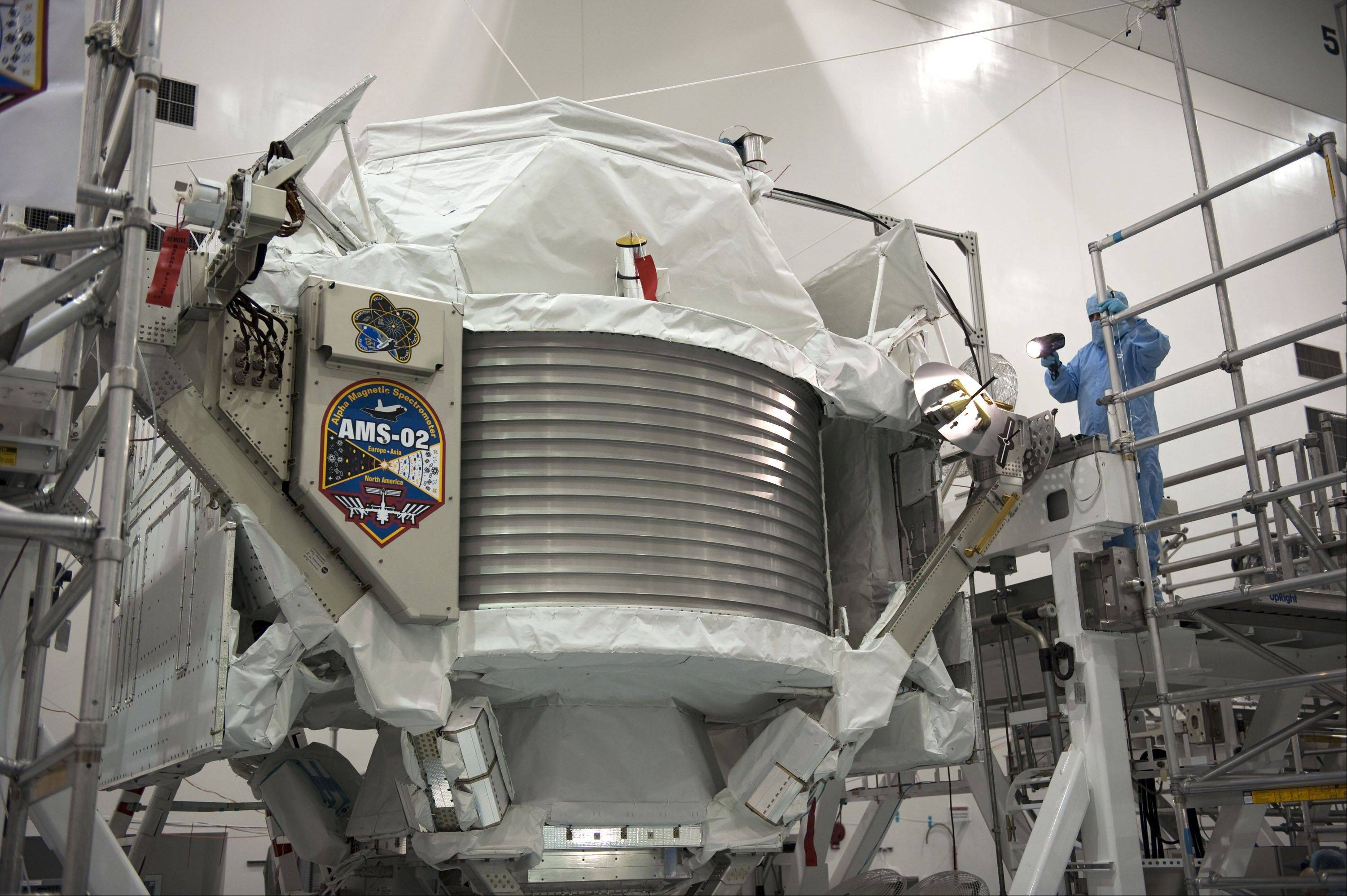 A technician examines the Alpha Magnetic Spectrometer at Kennedy Space Center in Cape Canaveral, Fla. An international team of scientists says the cosmic ray detector has found the first hint of dark matter, which has never yet been directly observed.