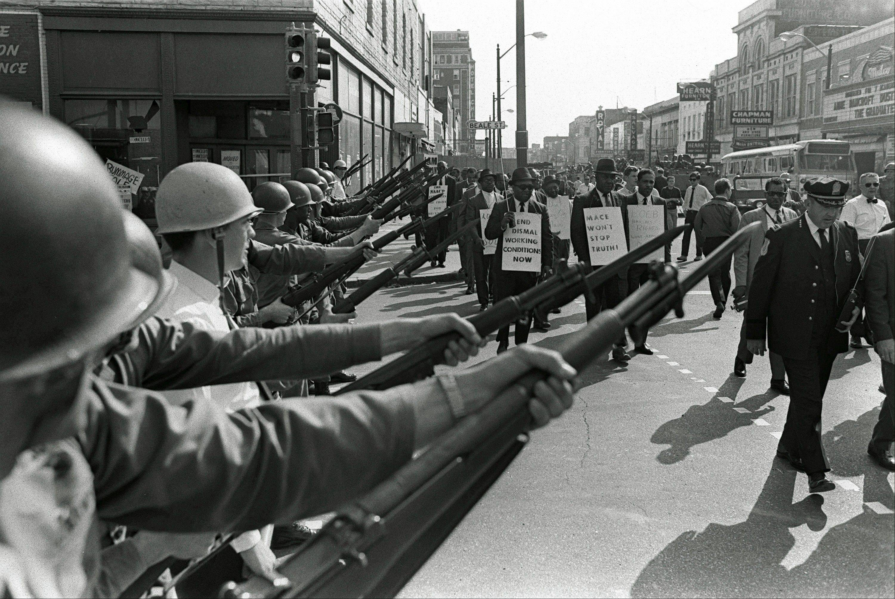In this March 29, 1968, photo, striking Memphis sanitation workers march past Tennessee National Guard troops with fixed bayonets during a 20-block march to City Hall. Forty-five years after Martin Luther King Jr. was killed supporting a historic sanitation workers strike in Memphis, the city's garbage and trash collectors are fighting to hold on to jobs that some city leaders want to hand over to a private company.