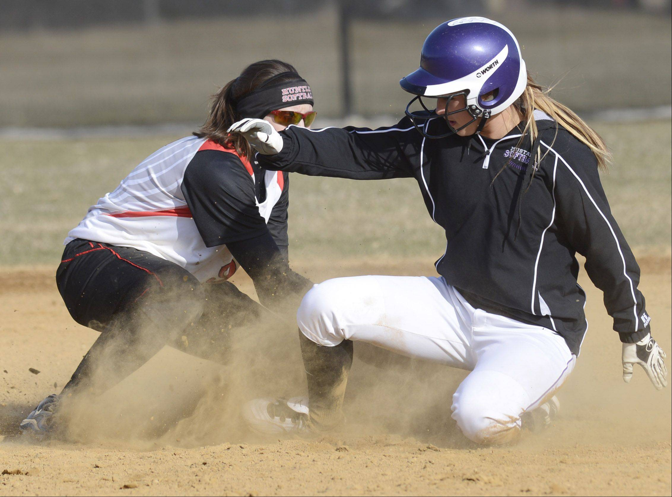 Rolling Meadow's Chloe Prodanovic slides safely into second base on a hit to right field as Huntley shortstop Miranda Peterson takes the throw during Wednesday's game.