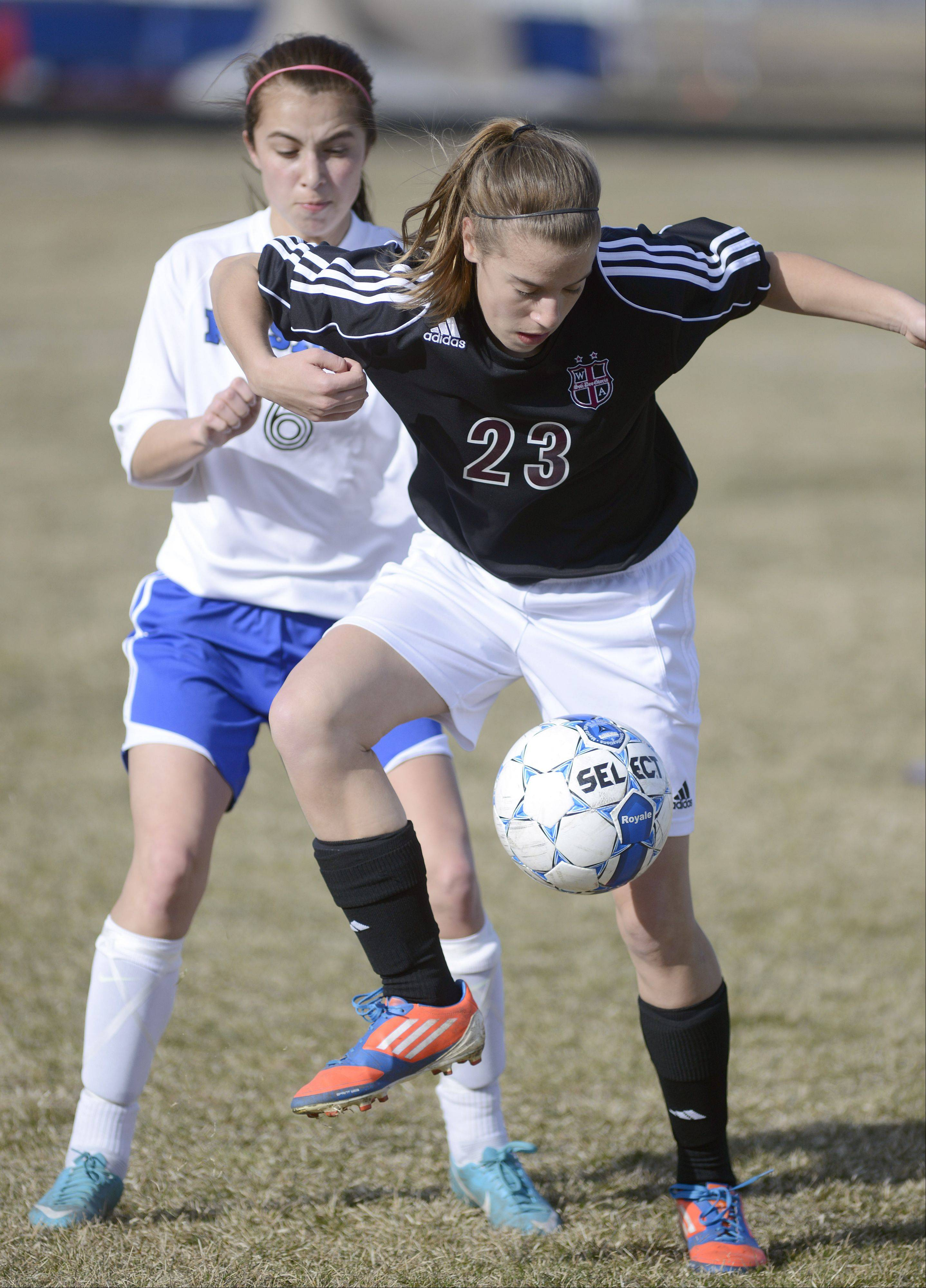 Wheaton Academy's Jamie Netzley keeps Rosary's Lizzie Kelly from the ball in the first half on Wednesday, April 3.