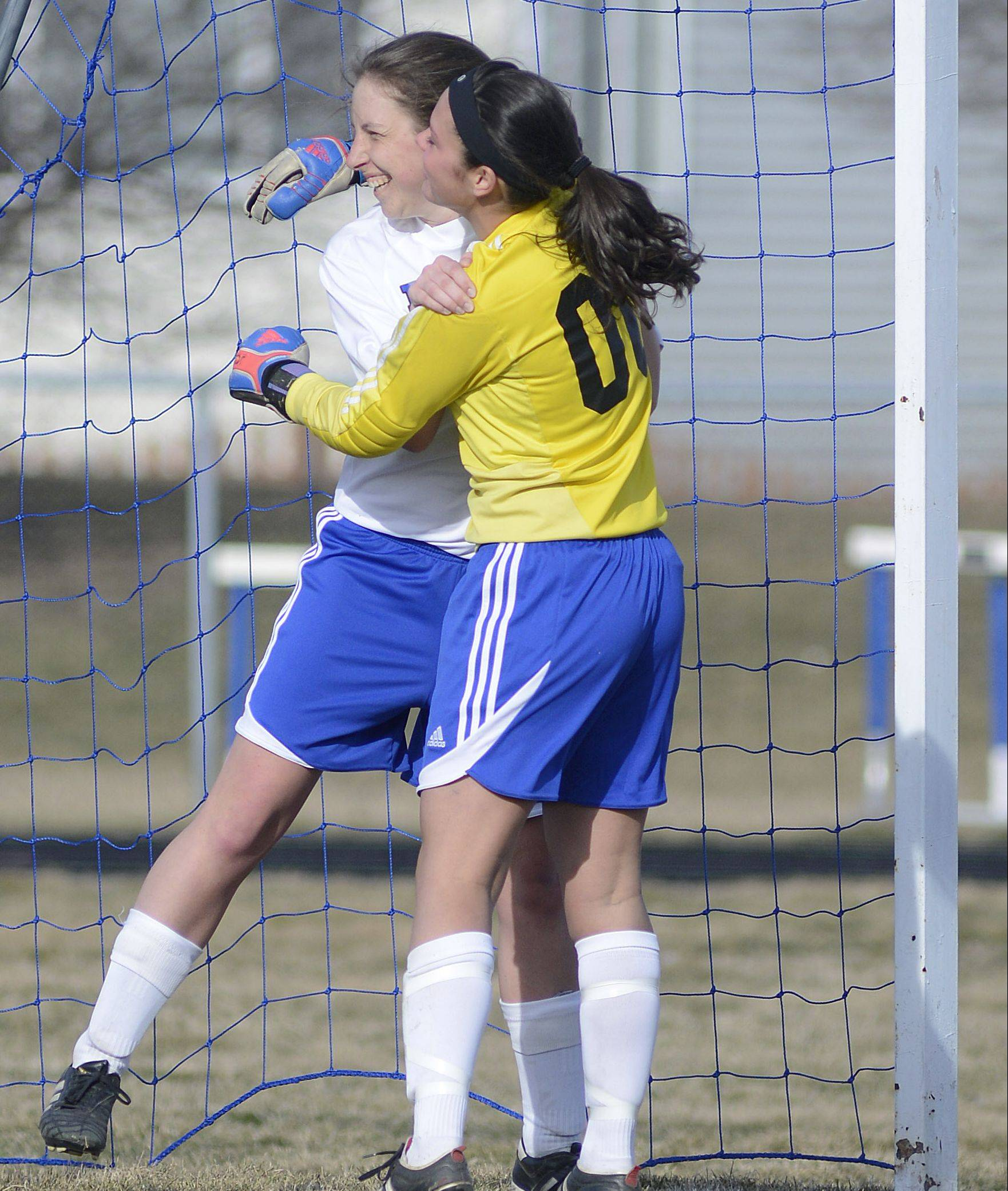 Rosary goalie Lauren Frasca embraces teammate Stephanie Ebert after Ebert deflected a ball and prevented a goal by Wheaton Academy in the first half on Wednesday, April 3.