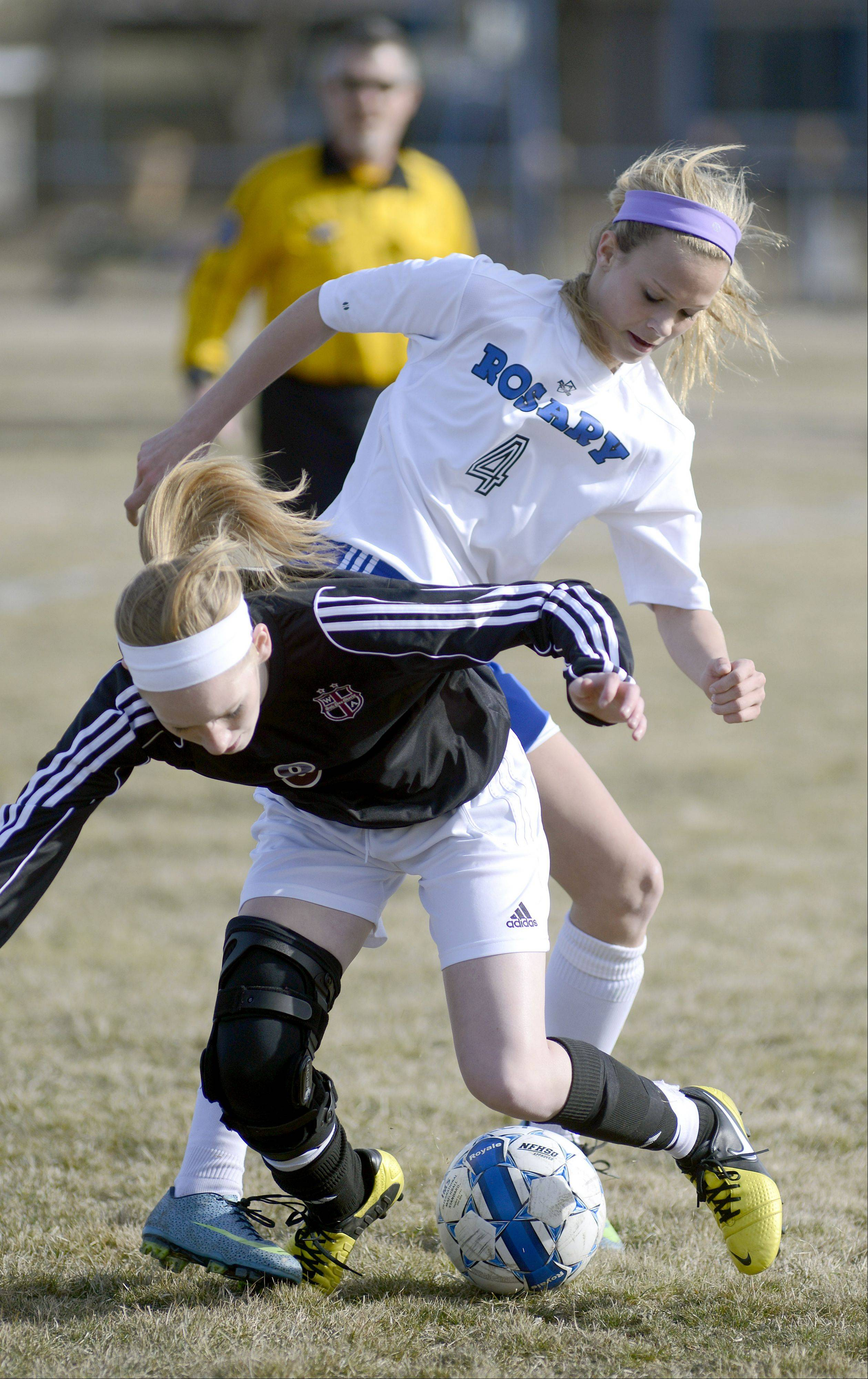 Wheaton Academy's Abbie Mercaldo tumbles to the ground after getting tangled with Rosary's Quincy Kellett in the first half on Wednesday, April 3.