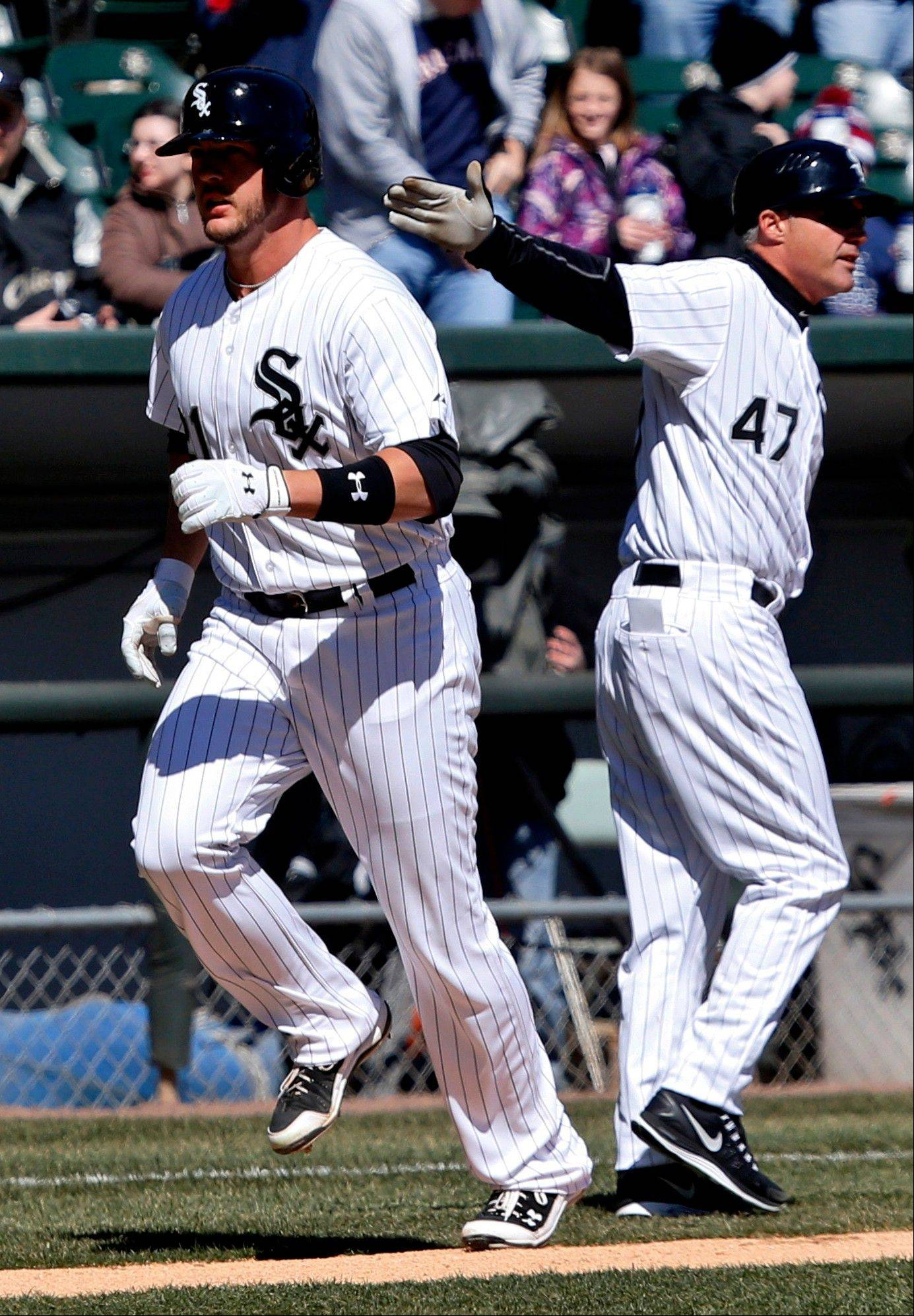 Chicago White Sox third base coach Joe McEwing, right, send Tyler Flowers home after Flower's home run off Kansas City Royals starting pitcher Ervin Santana during the third inning of a baseball game Wednesday, April 3, 2013, in Chicago.