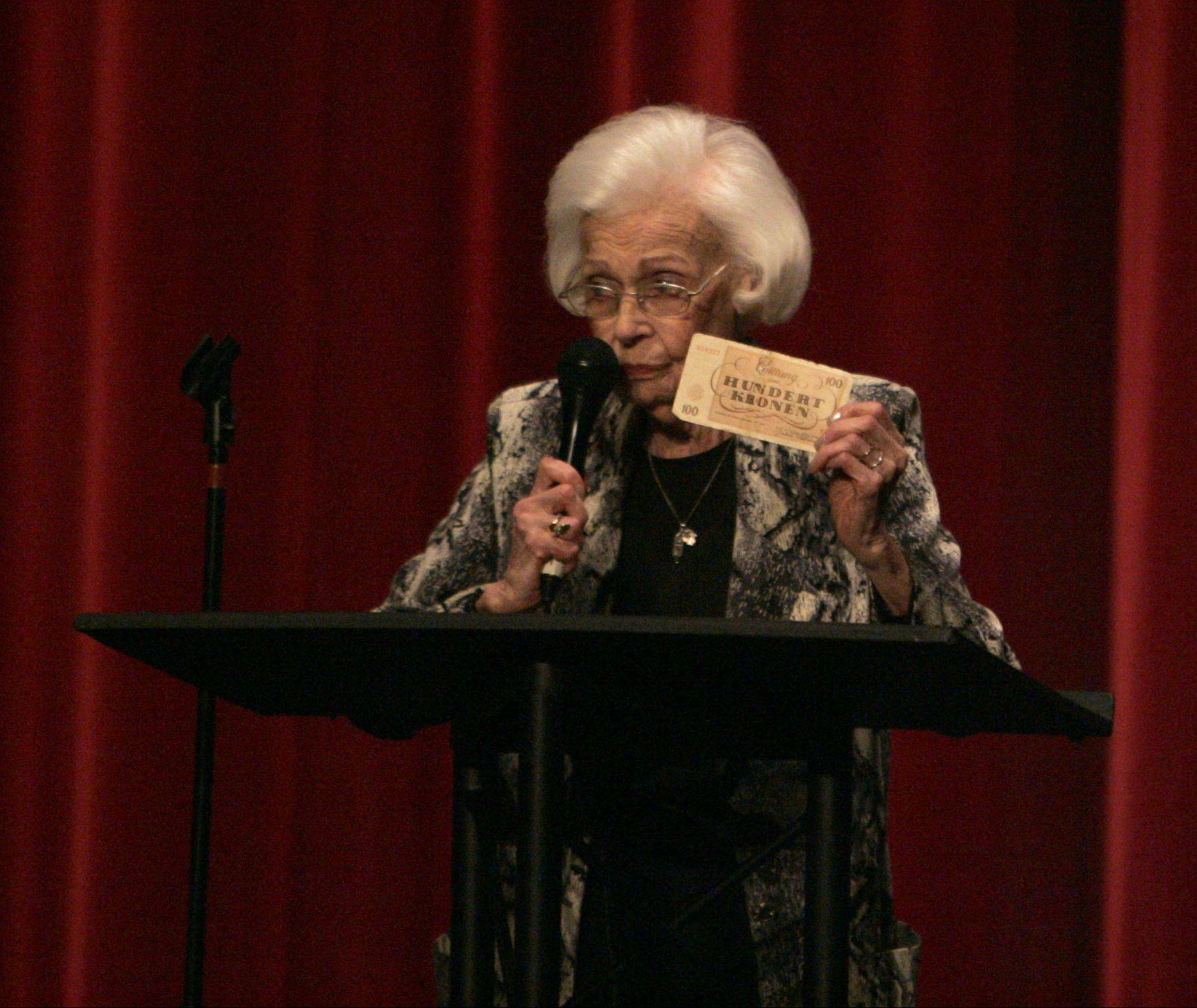 Lisl Bogart, originally from Prague, talks to Huntley High School students Wednesday about her time spent in Theresienstadt, a Nazi concentration camp. Bogart still has her badge she was forced to wear identifying her as a Jew, and also some of the fake money that was made to fool the Red Cross when they visited her concentration camp.