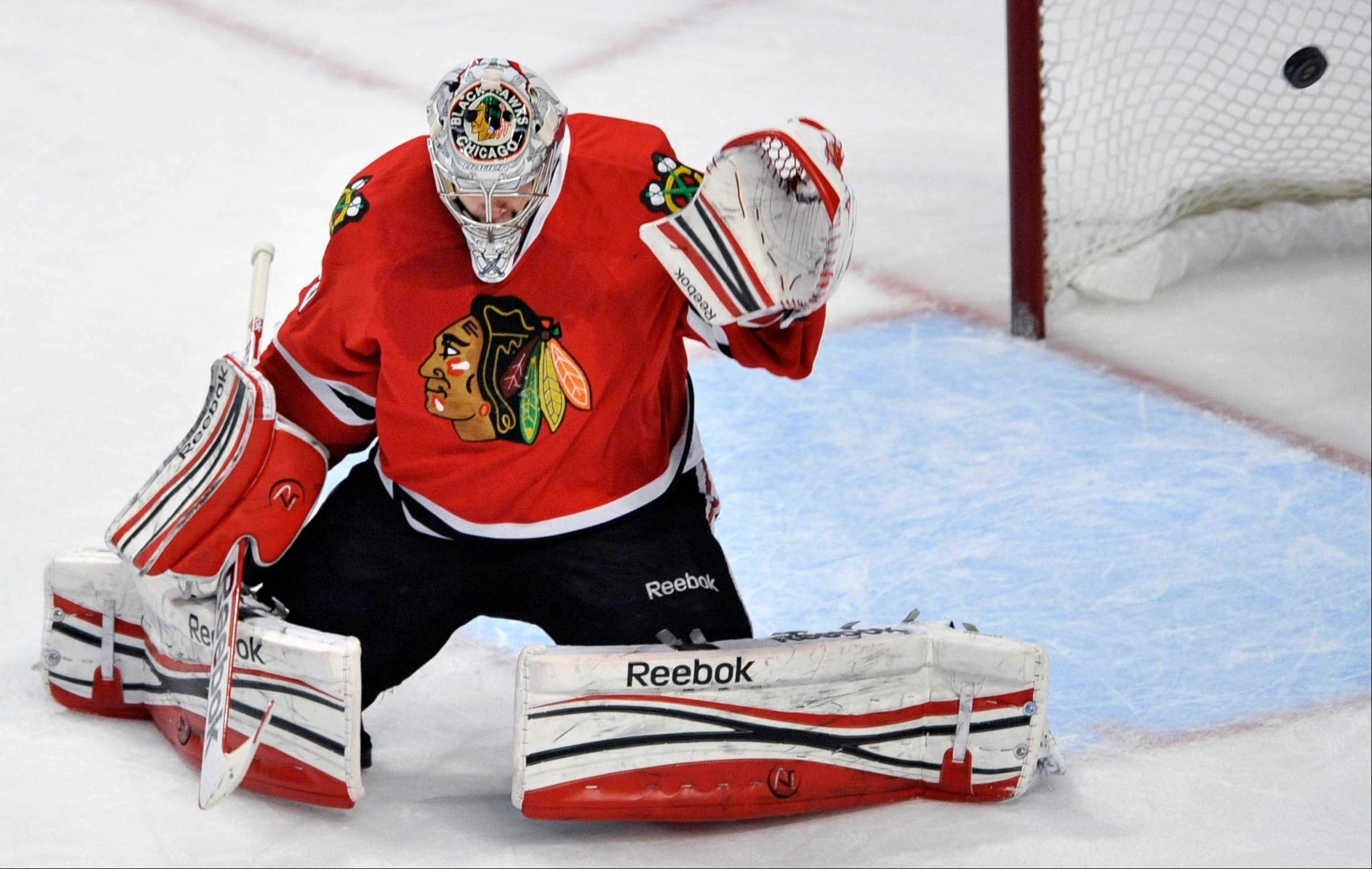 Chicago Blackhawks goalie Corey Crawford misses a goal scored by St. Louis Blues' Adam Cracknell during the first period of an NHL hockey game in Chicago, Thursday, April, 4, 2013. (AP Photo/Paul Beaty)