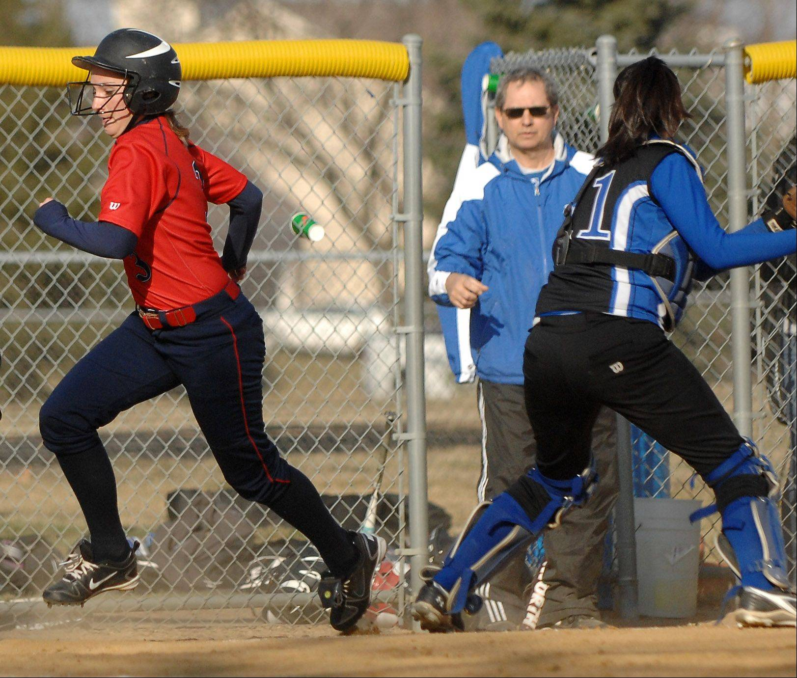 West Aurora�s Hannah Banks heads home to score on a botched Rosary rundown during Thursday�s game in Aurora.