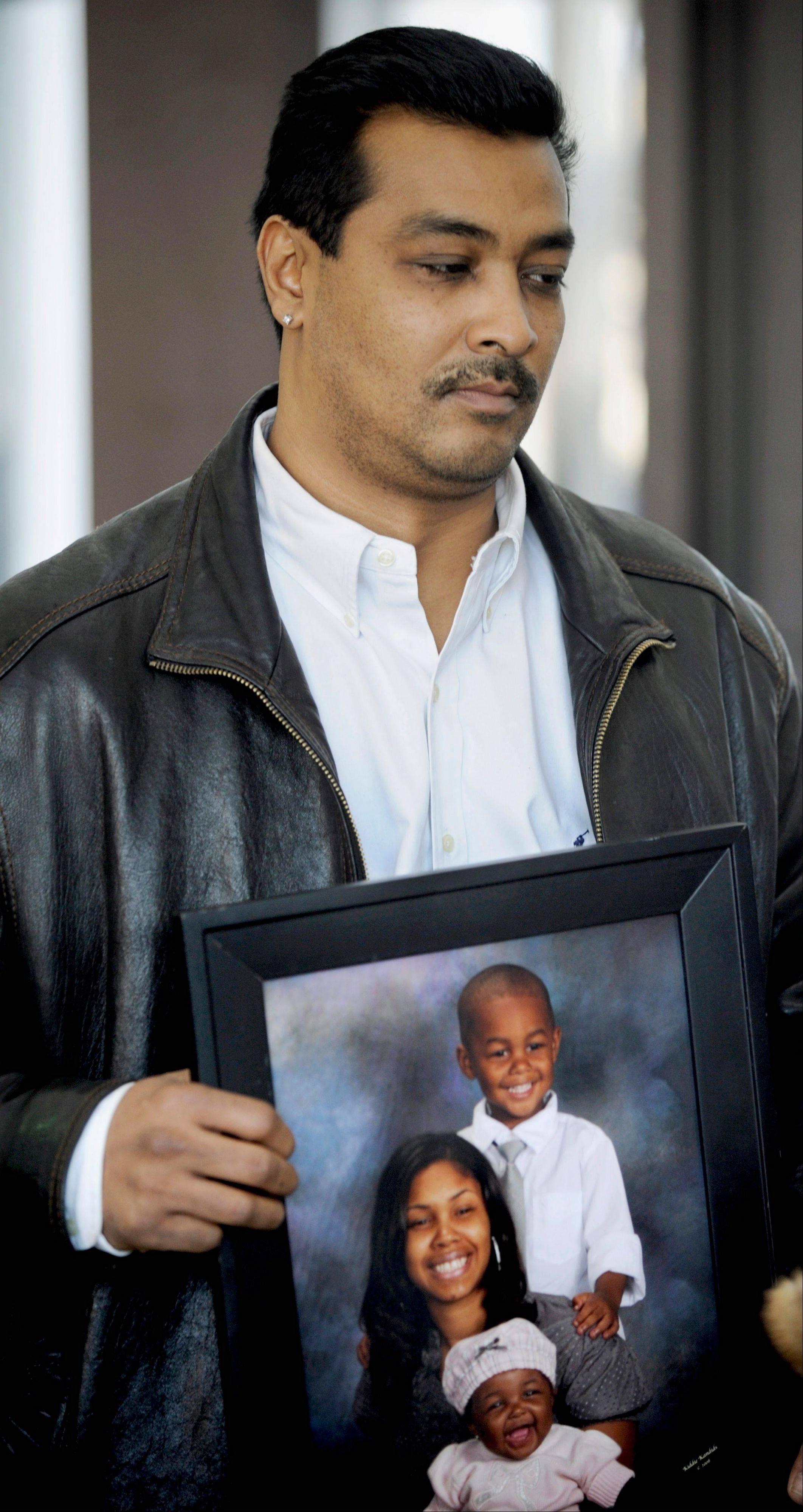 FILE - In this Feb. 23, 2009 file photo, Keith Henry holds a photo of his daughter Nova Henry, with her daughter Ava and son at the Cook County Courthouse in Chicago. Chicago attorney Fredrick Goings, who was convicted in the January 2009 slayings of Nova and daughter Ava, the ex-girlfriend and daughter of former NBA center Eddy Curry, was sentenced Thursday, April 4, 2013, to life in prison. Goings represented Henry in a child custody case against Curry, and was romantically involved with her. (AP Photo/Paul Beaty, File)